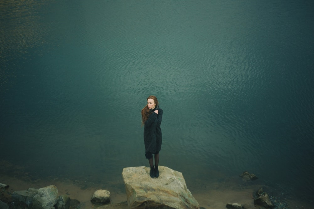woman standing on large gray rock along body of water