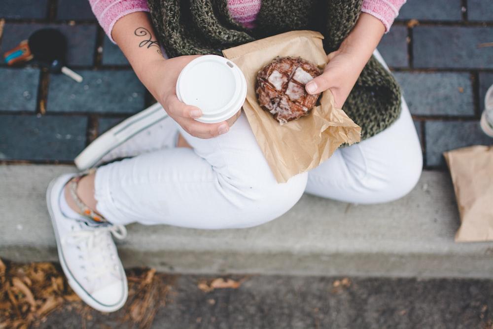 person sitting while holding white tumbler