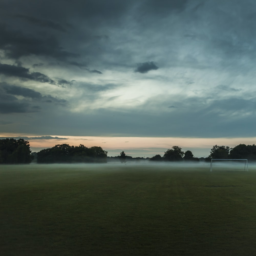 brown soccer field under cloudy sky