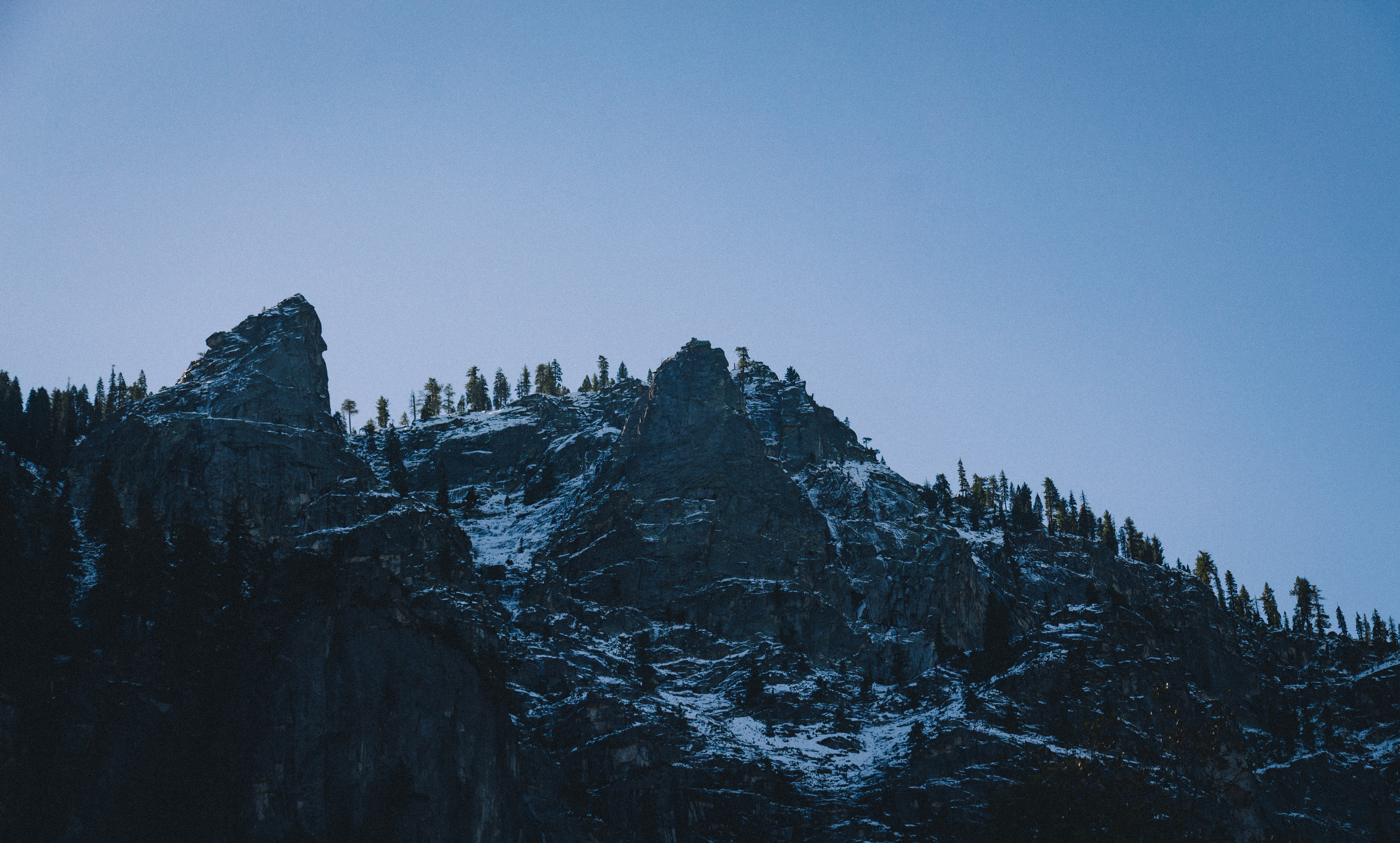 The forest mixes with snow on a rocky mountainside in Yosemite Valley