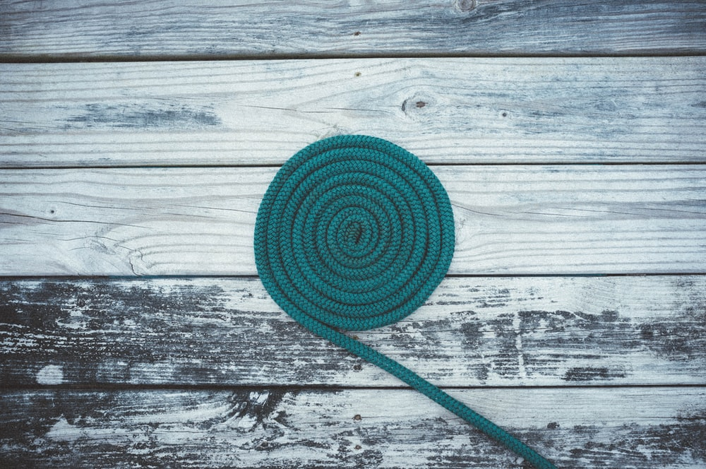 closeup photo of green coil on gray wooden board