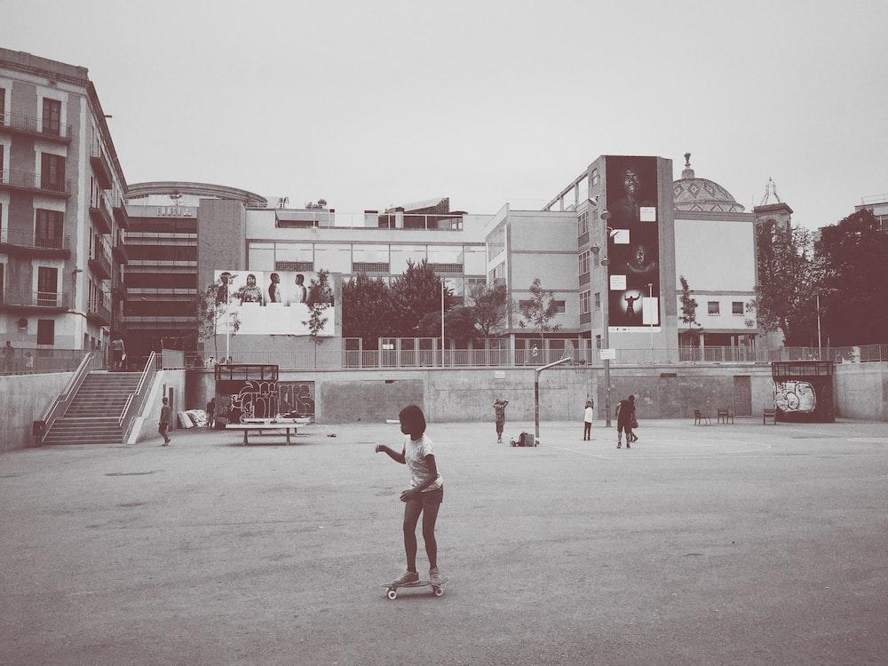 girl ride on skateboard near building