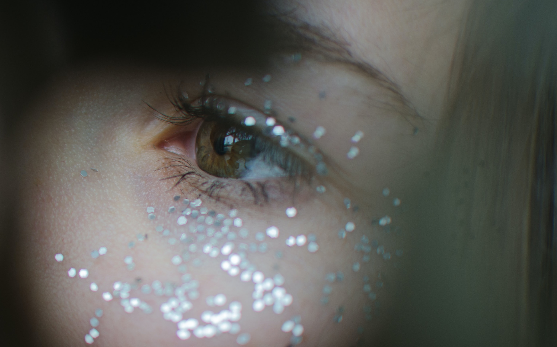 Close-up of glitter around a woman's eye