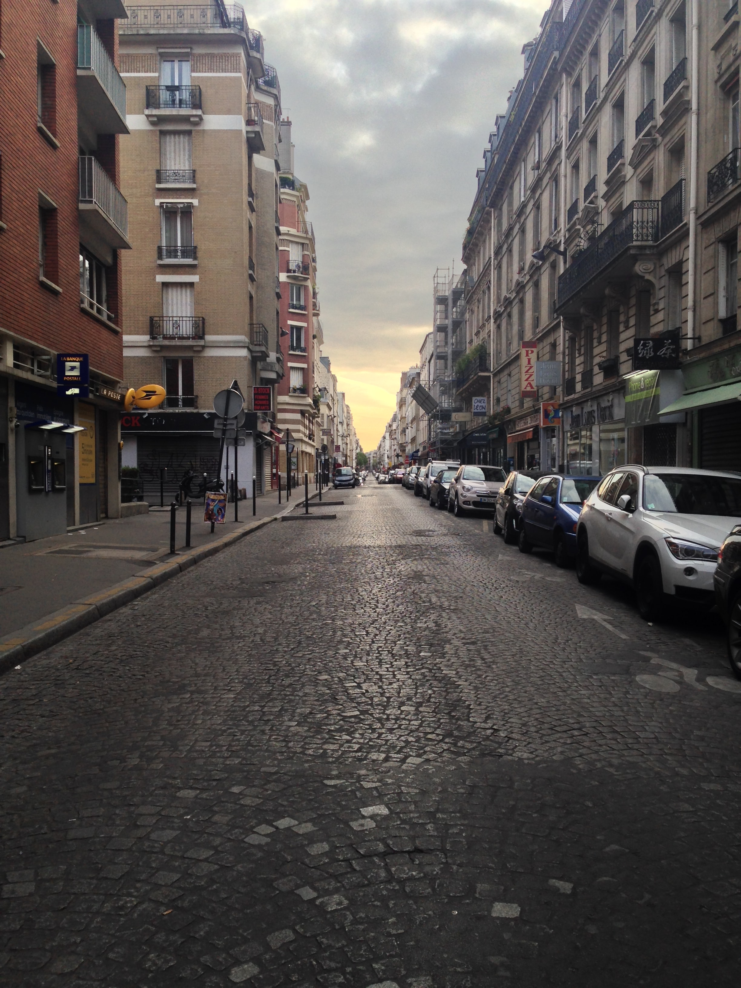 A cobblestone city street with urban buildings in Paris, France.