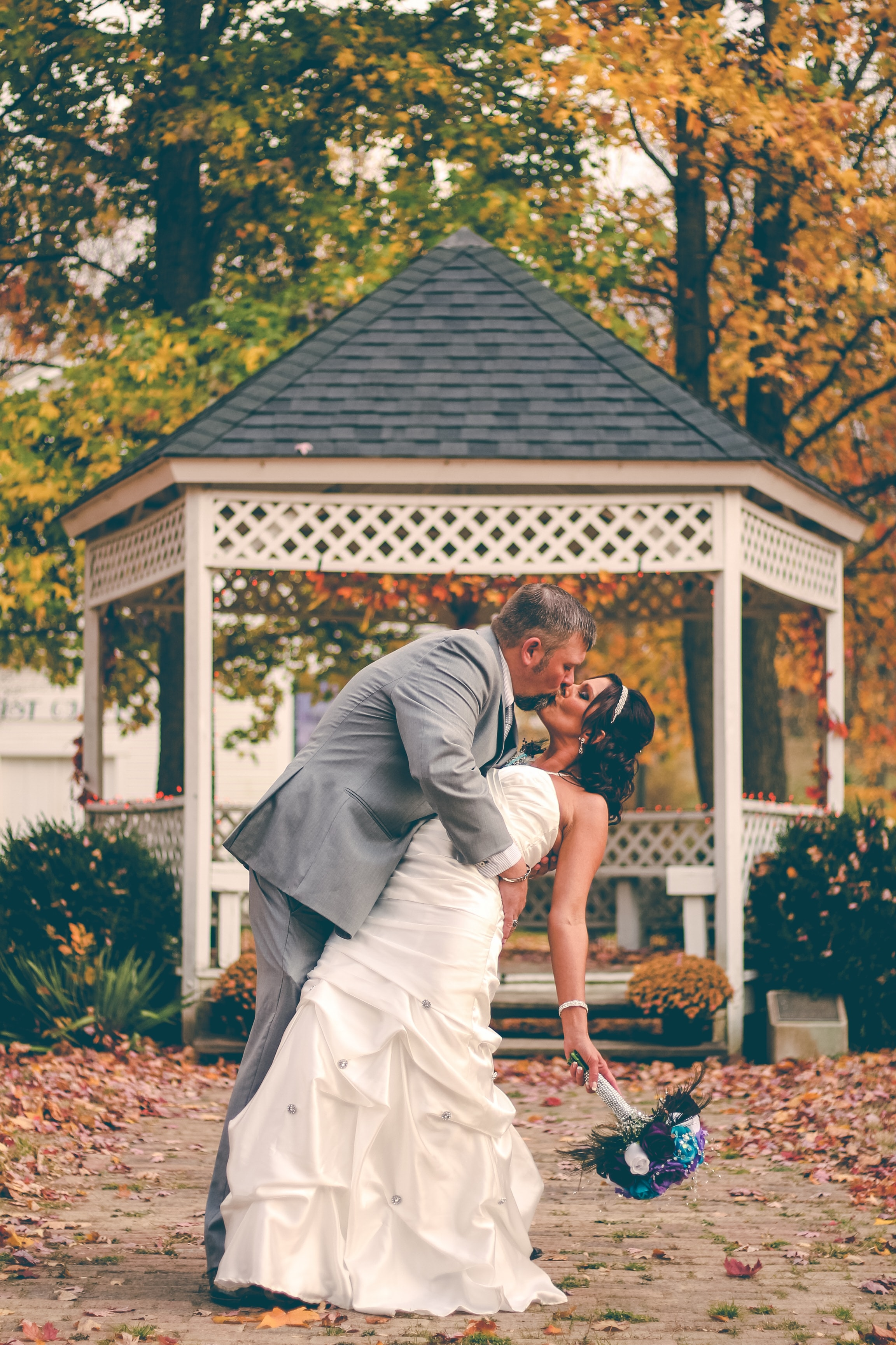 groom kissing bride near white gazebo