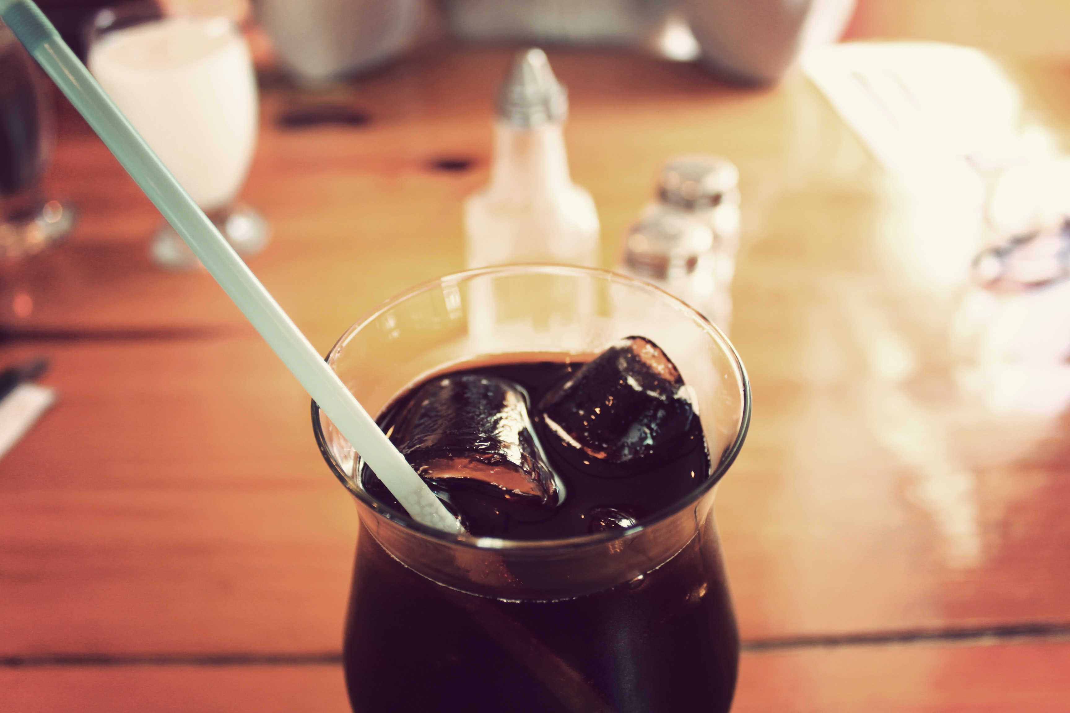 Refreshing glass of soda with ice and a straw at a diner