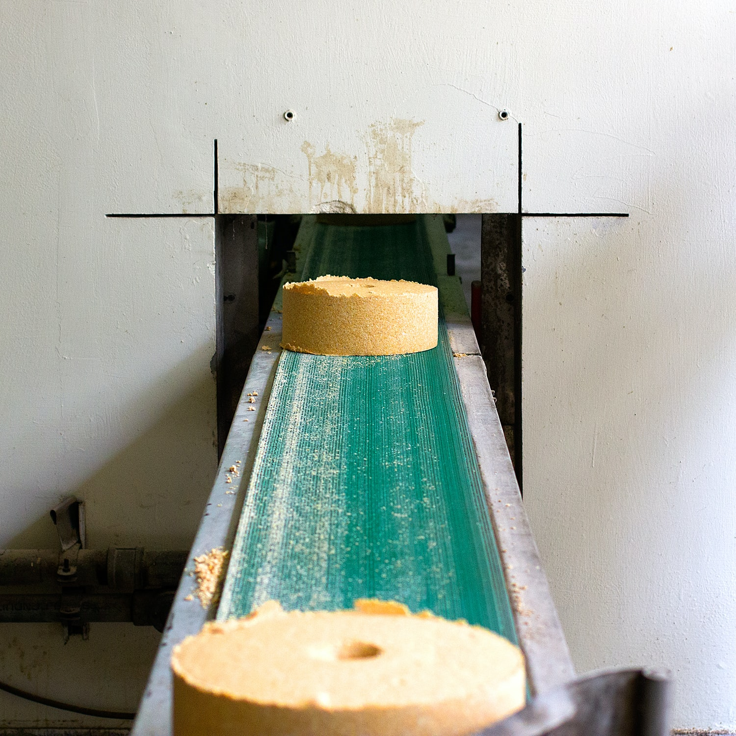 A yellow circular wheel on a green conveyer belt exiting a square hole in the white wall