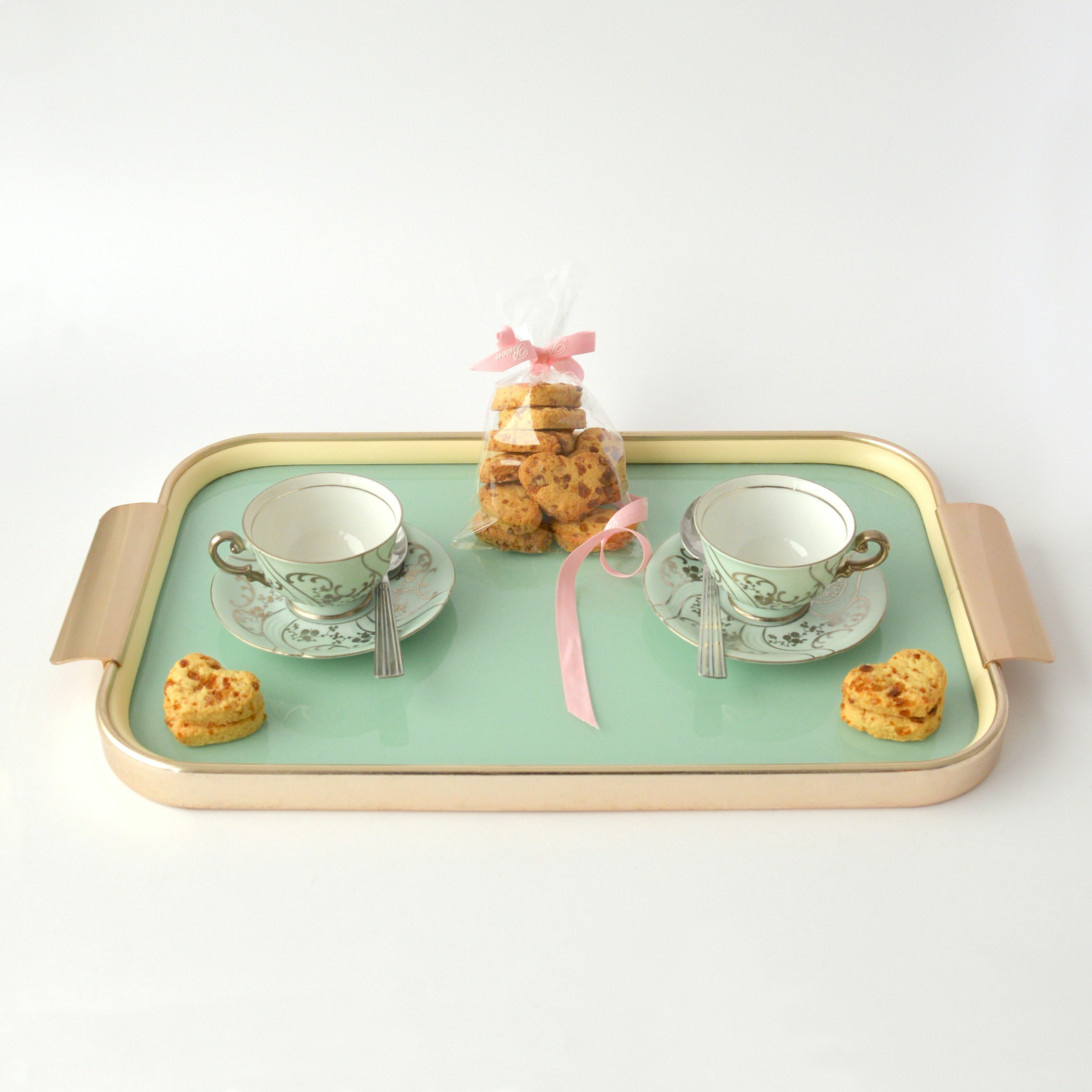A tray with two teacups on saucers and a bag of cookies on a white surface