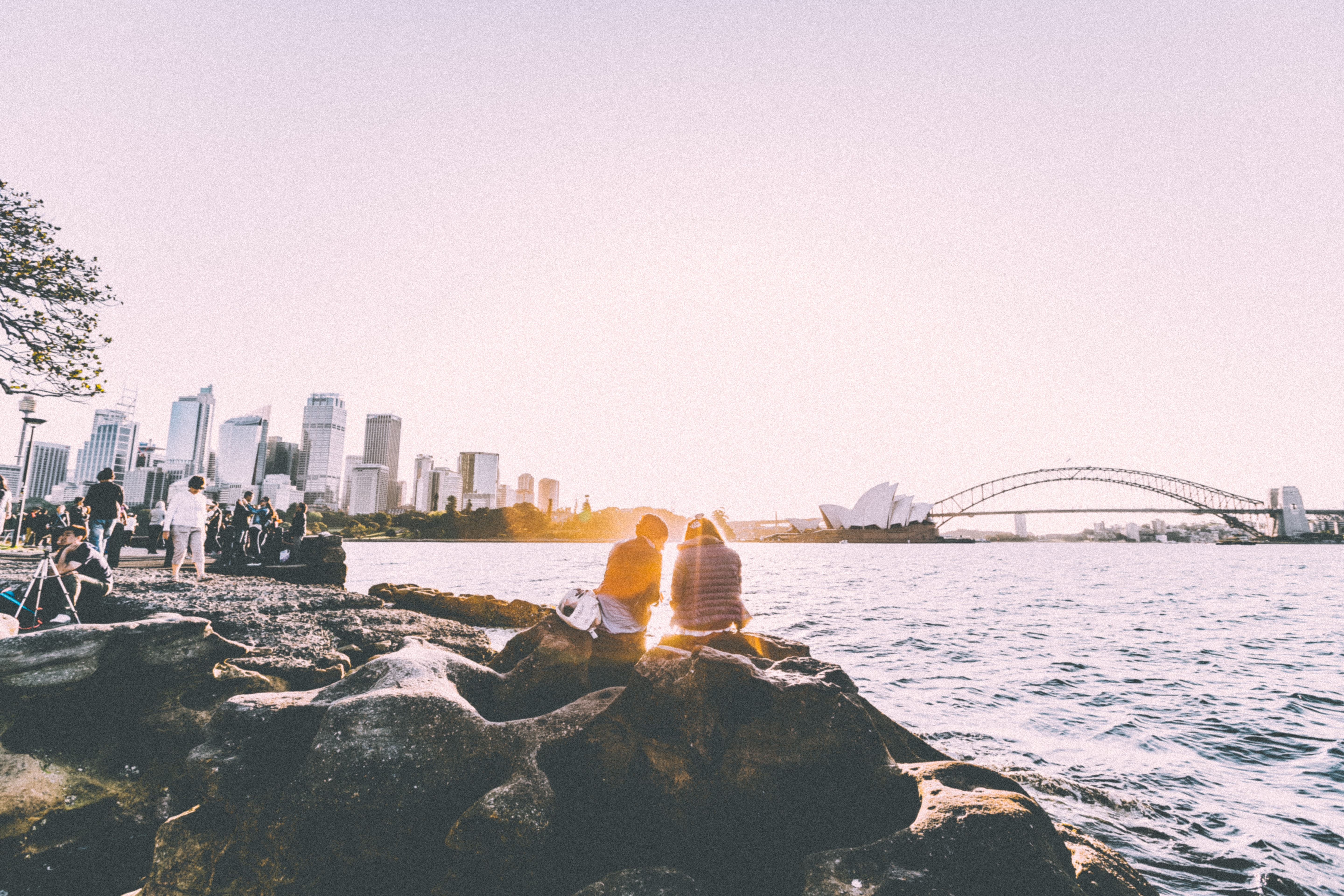 people sitting and standing at shore watching the sunset near the Sydney Opera House in panorama photography