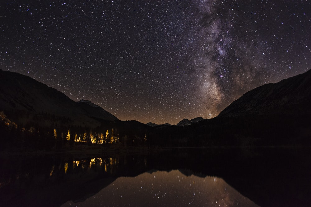 mountain reflecting on body of water at nighttime