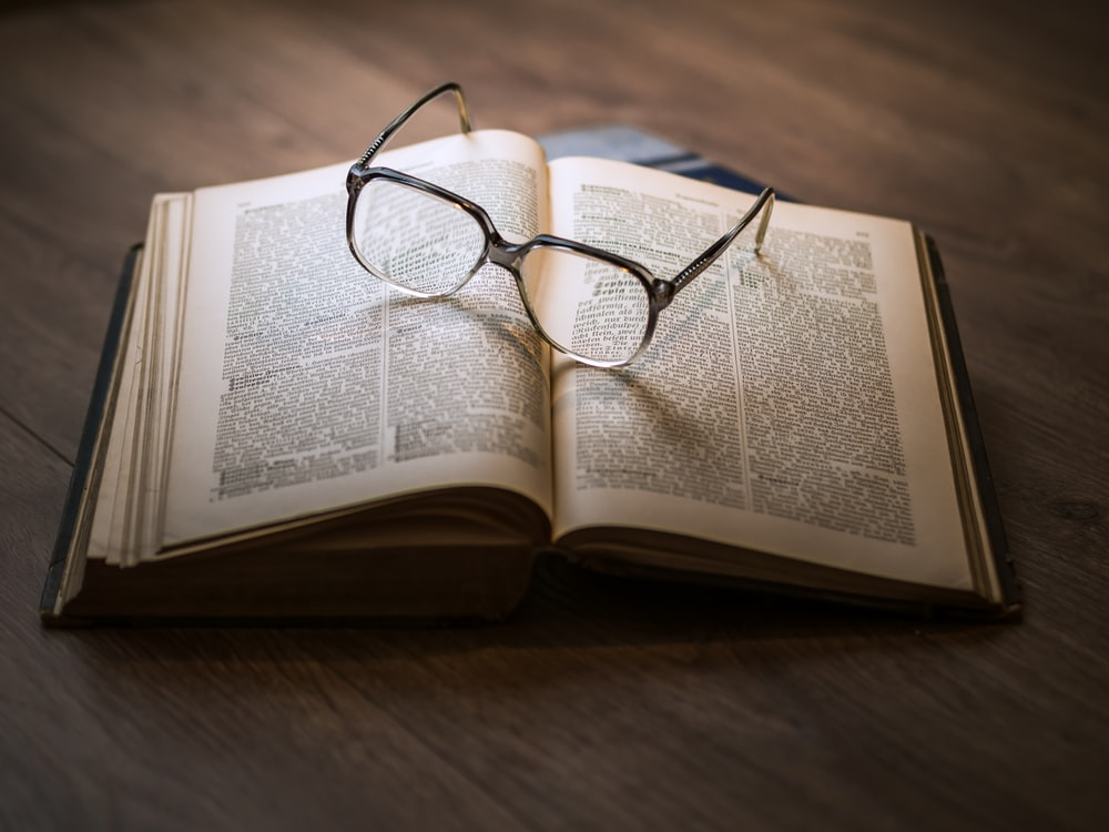 framed eyeglasses on top open book best story writers