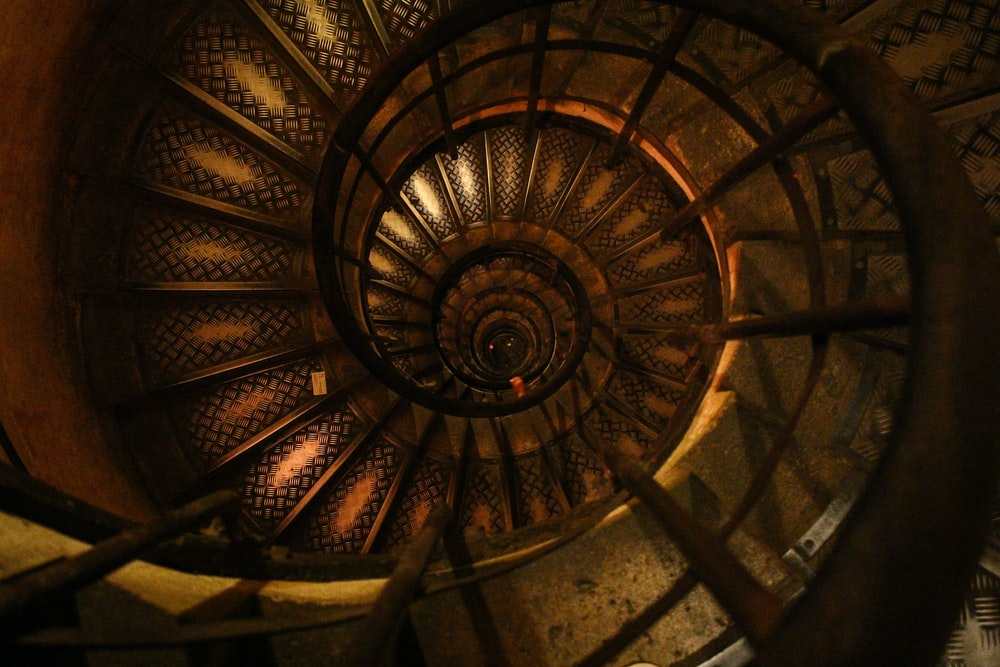 A worn spiral staircase with dark wood and faded designs