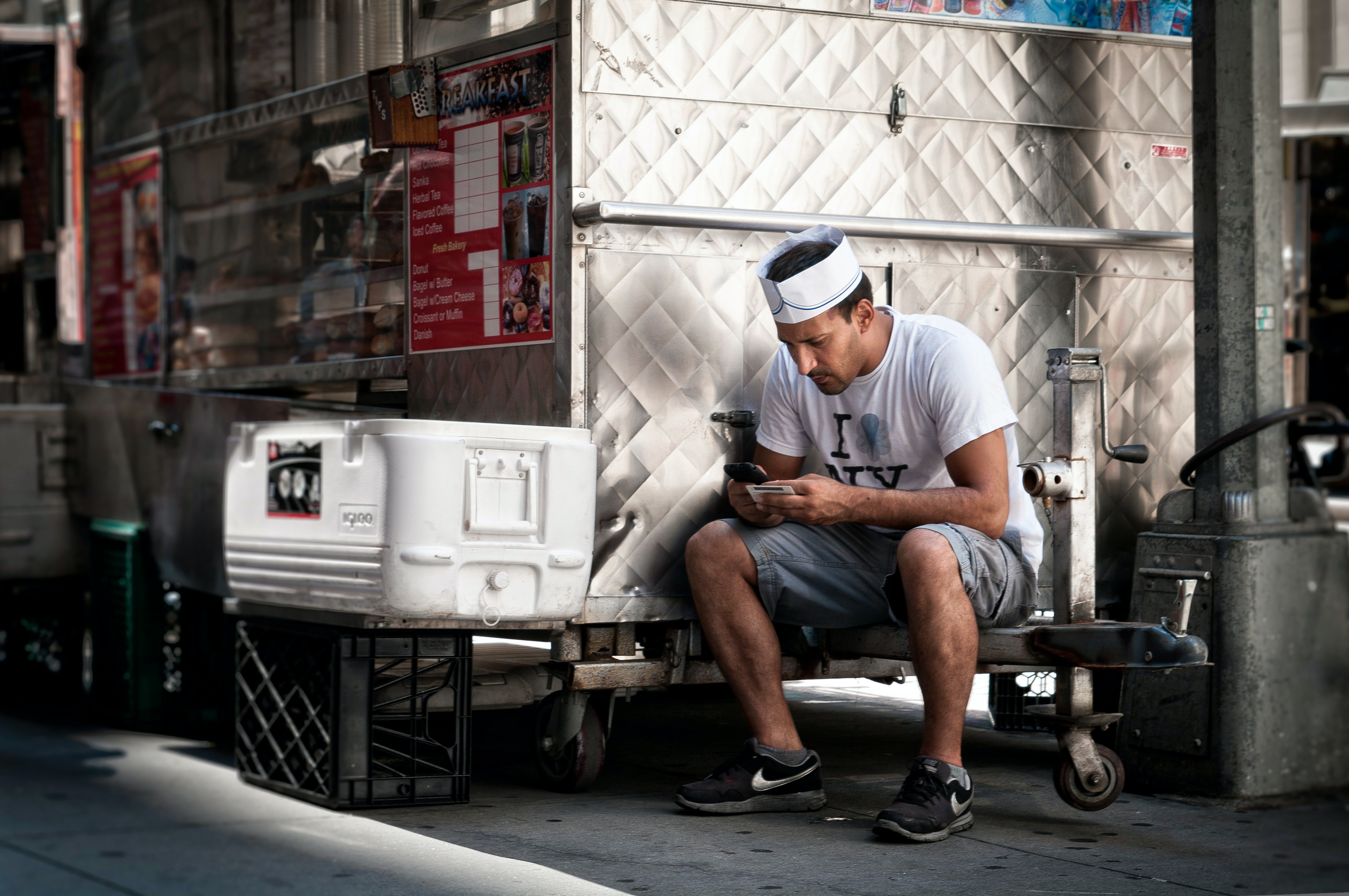 A man sits on the side of a food truck using his cell phone