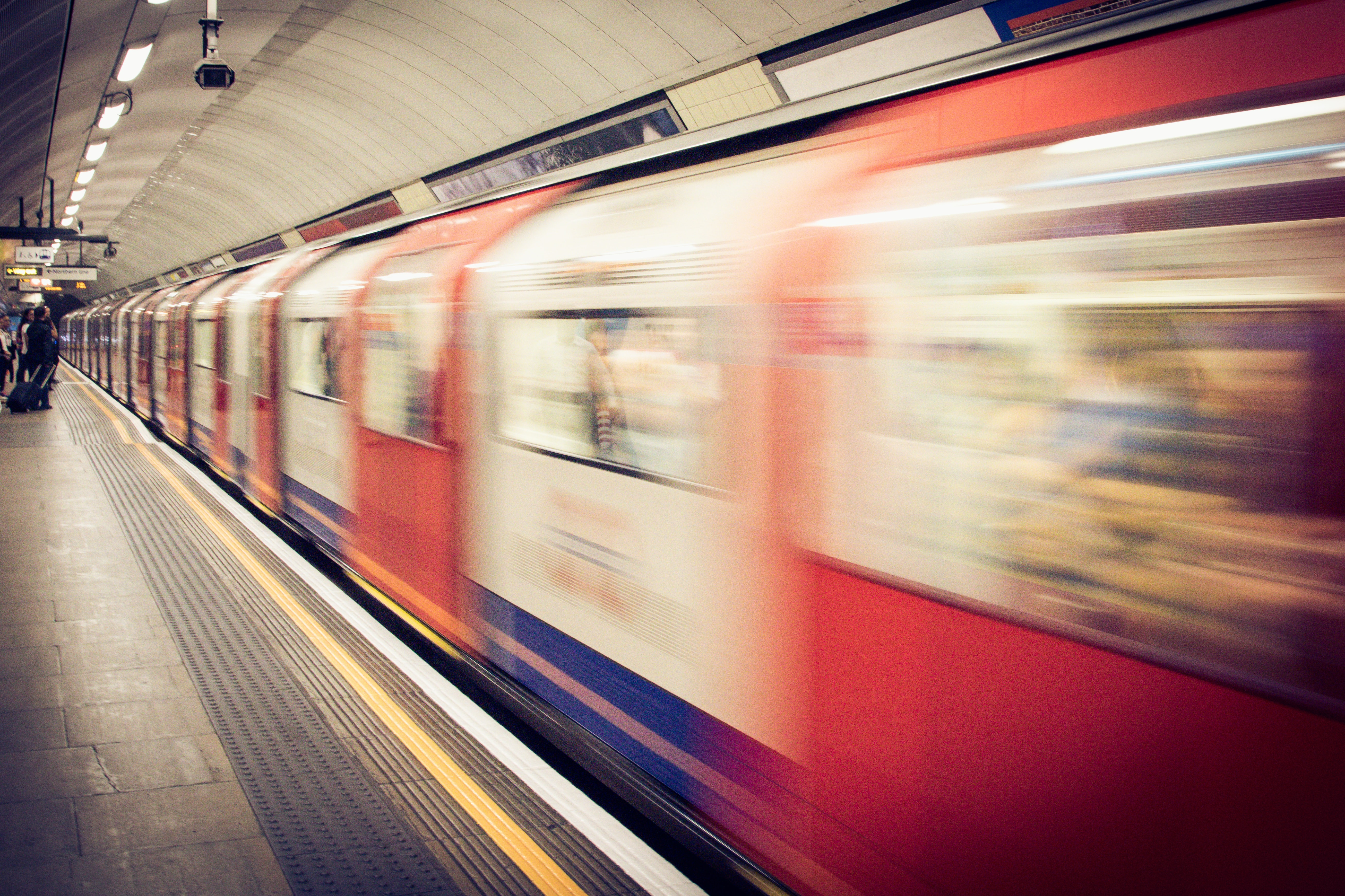 Tube train passing station with motion blur as passengers wait in the United Kingdom