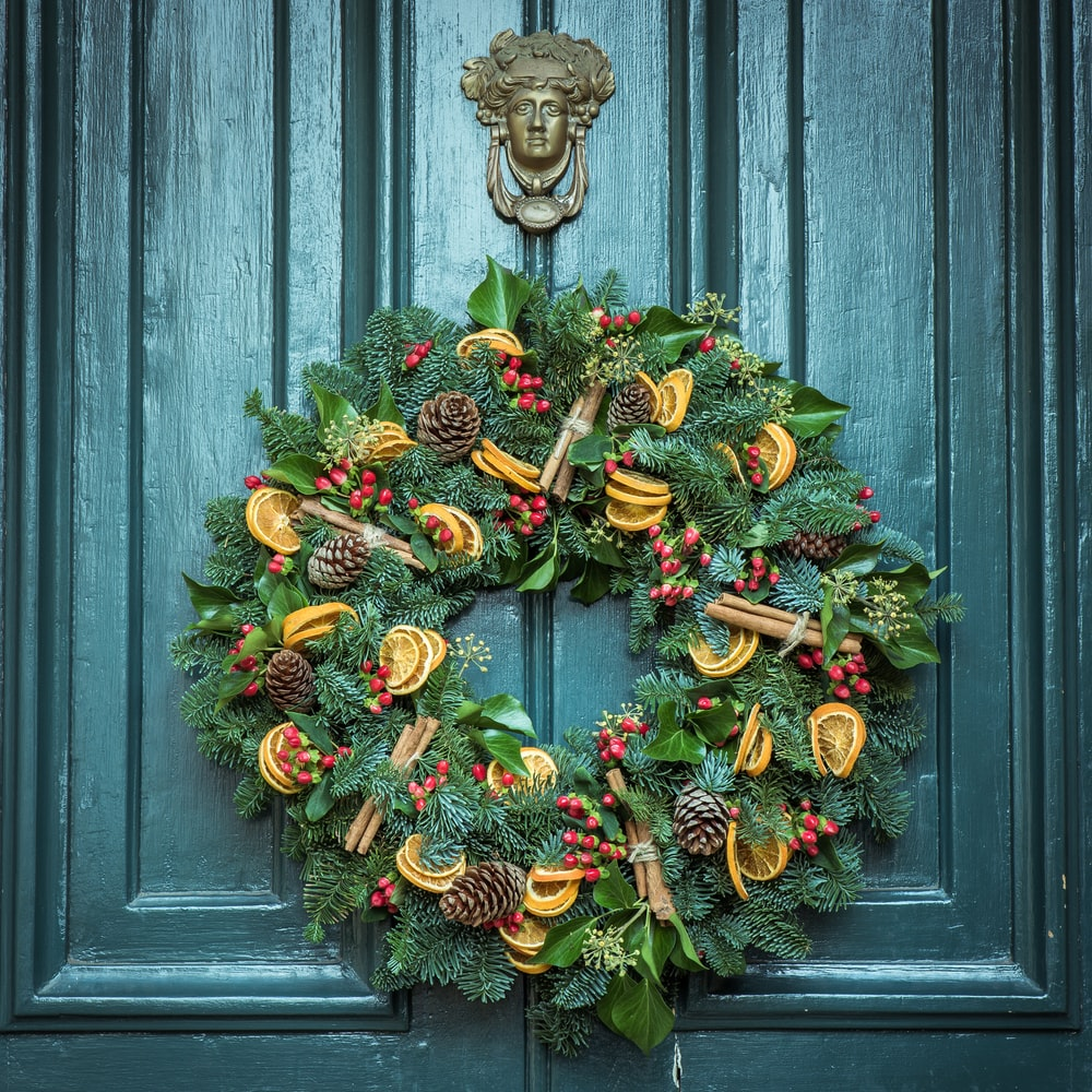 photo of green door wreath mounted in green wooden door