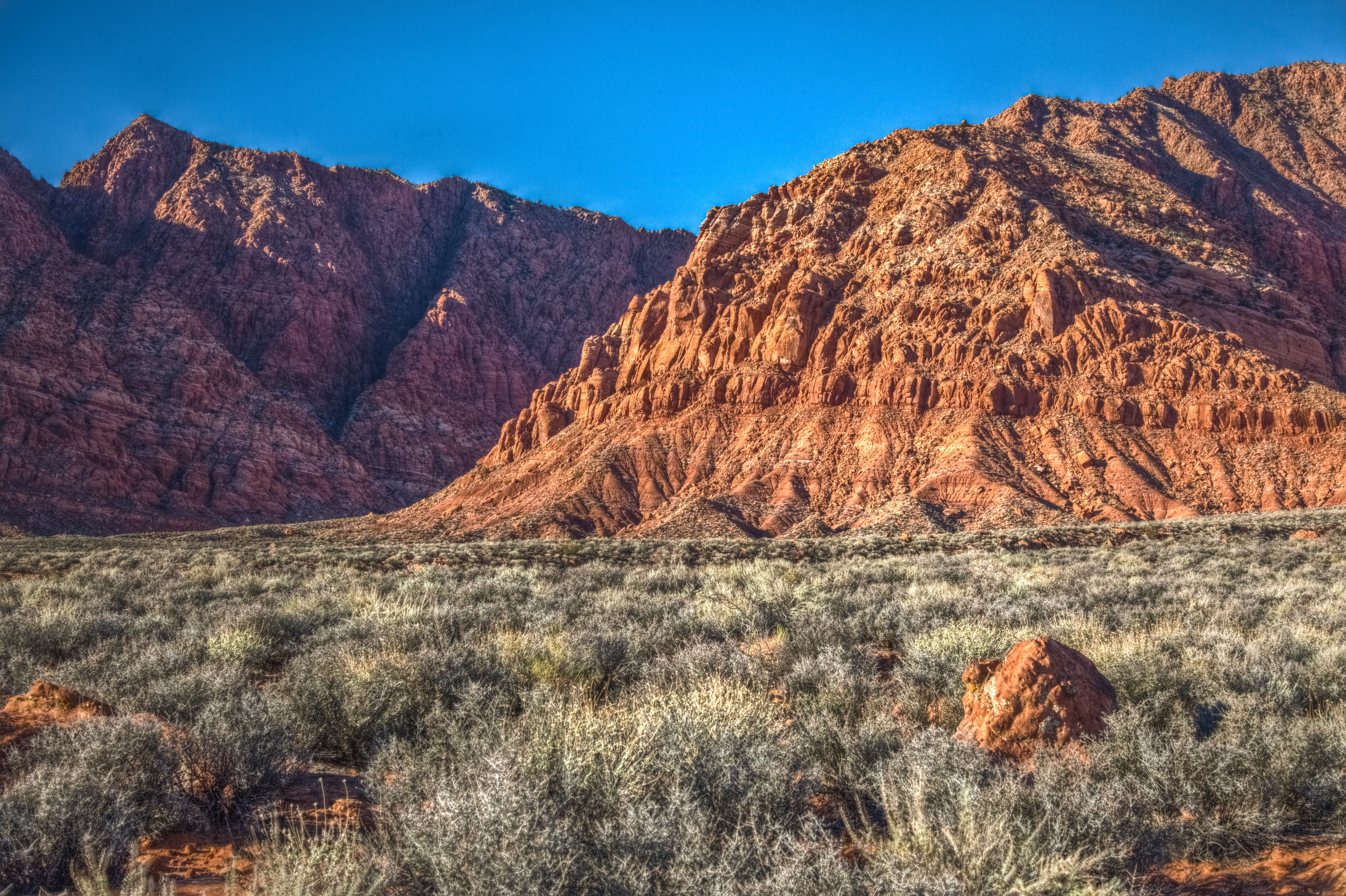 Red rocky mountains in a grassy desert valley