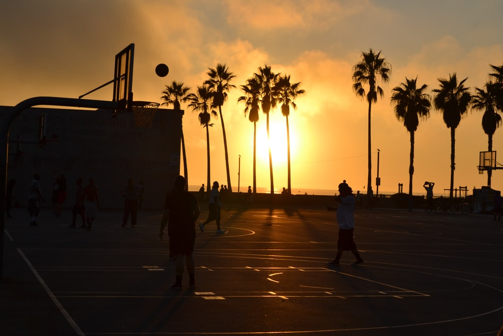 silhouette photo of people playing basketball during sunset