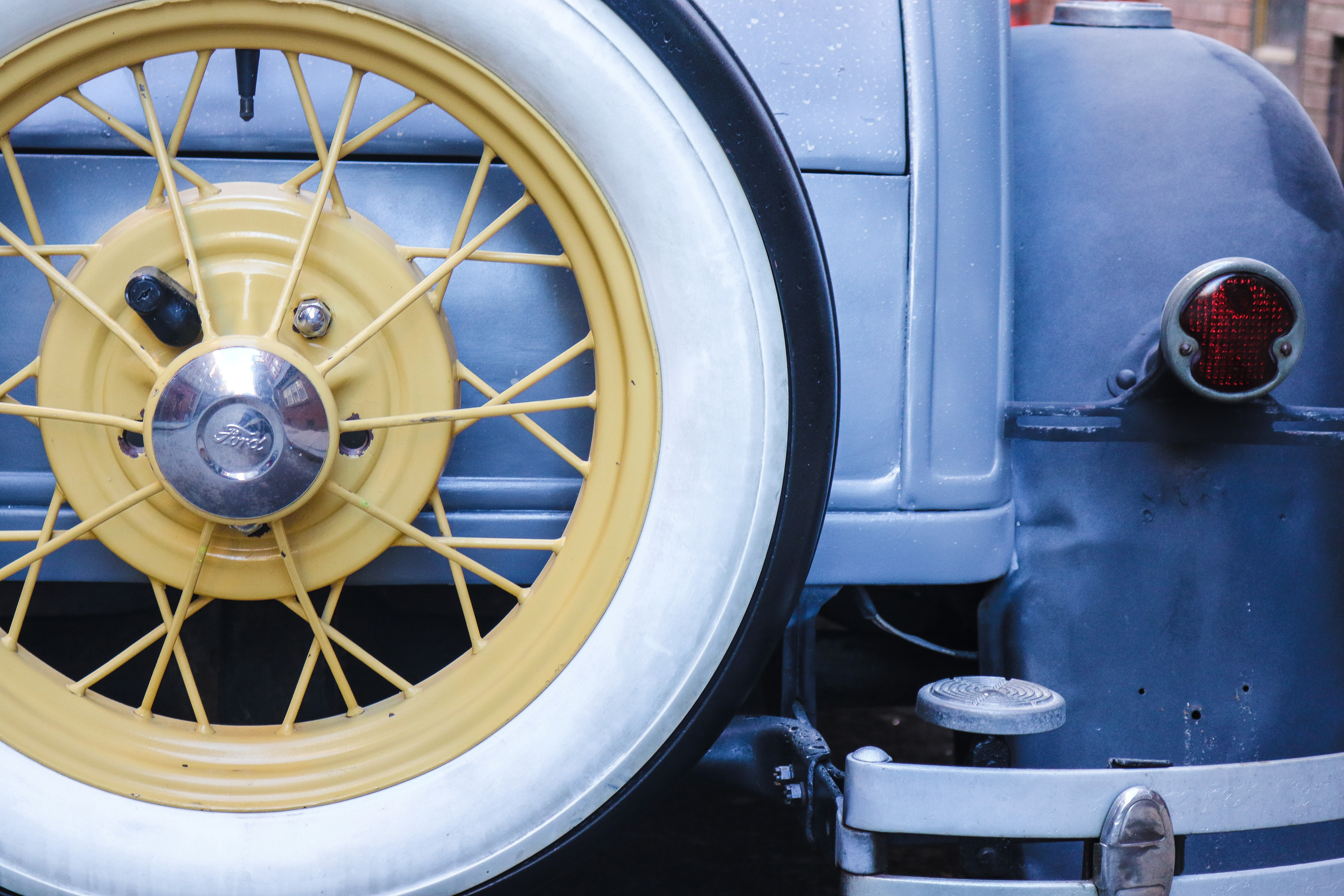 Vintage, blue car with classic white rim tire mounted on back