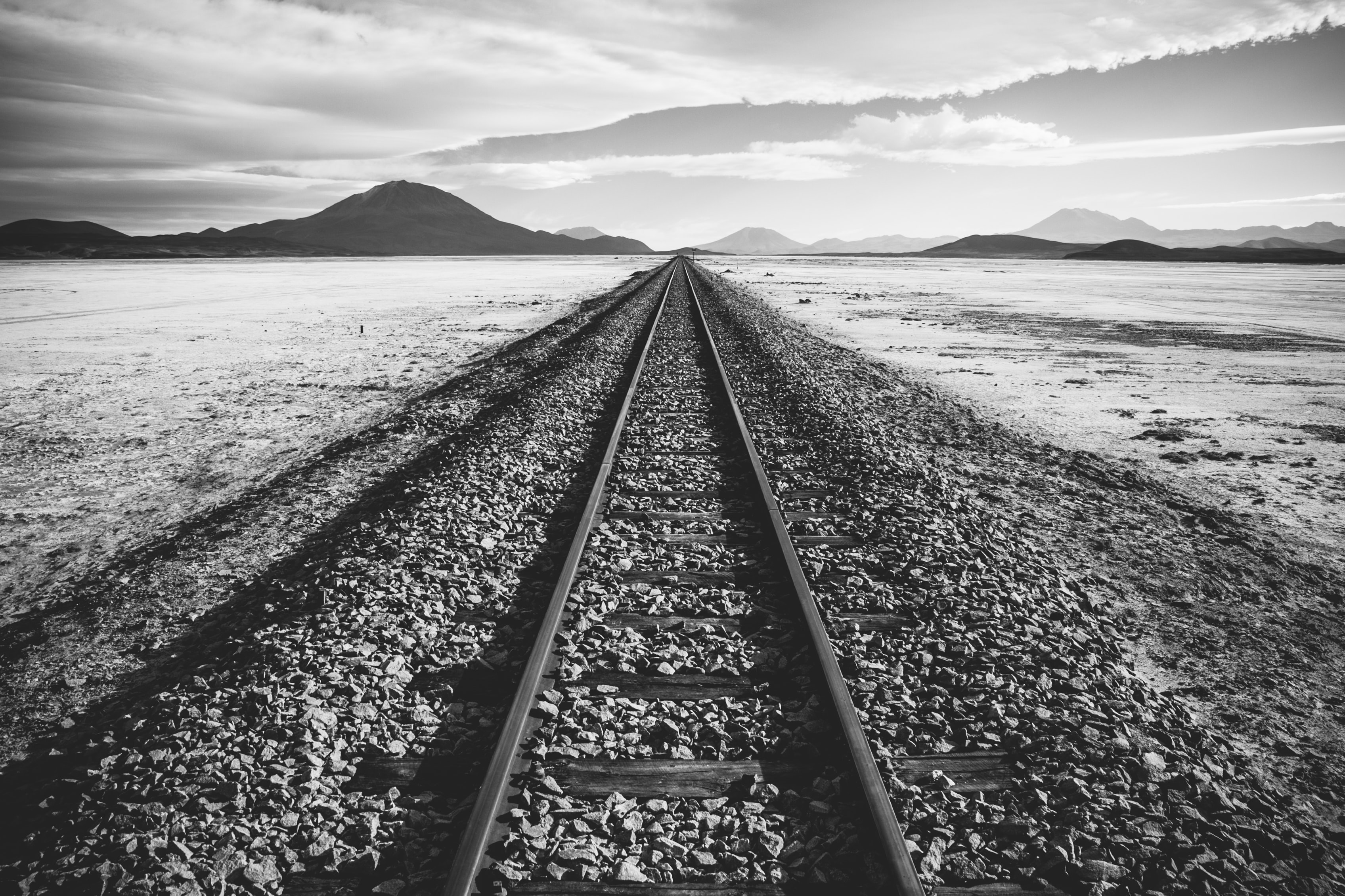 A black-and-white shot of a railway track through a barren wilderness in Bolivia