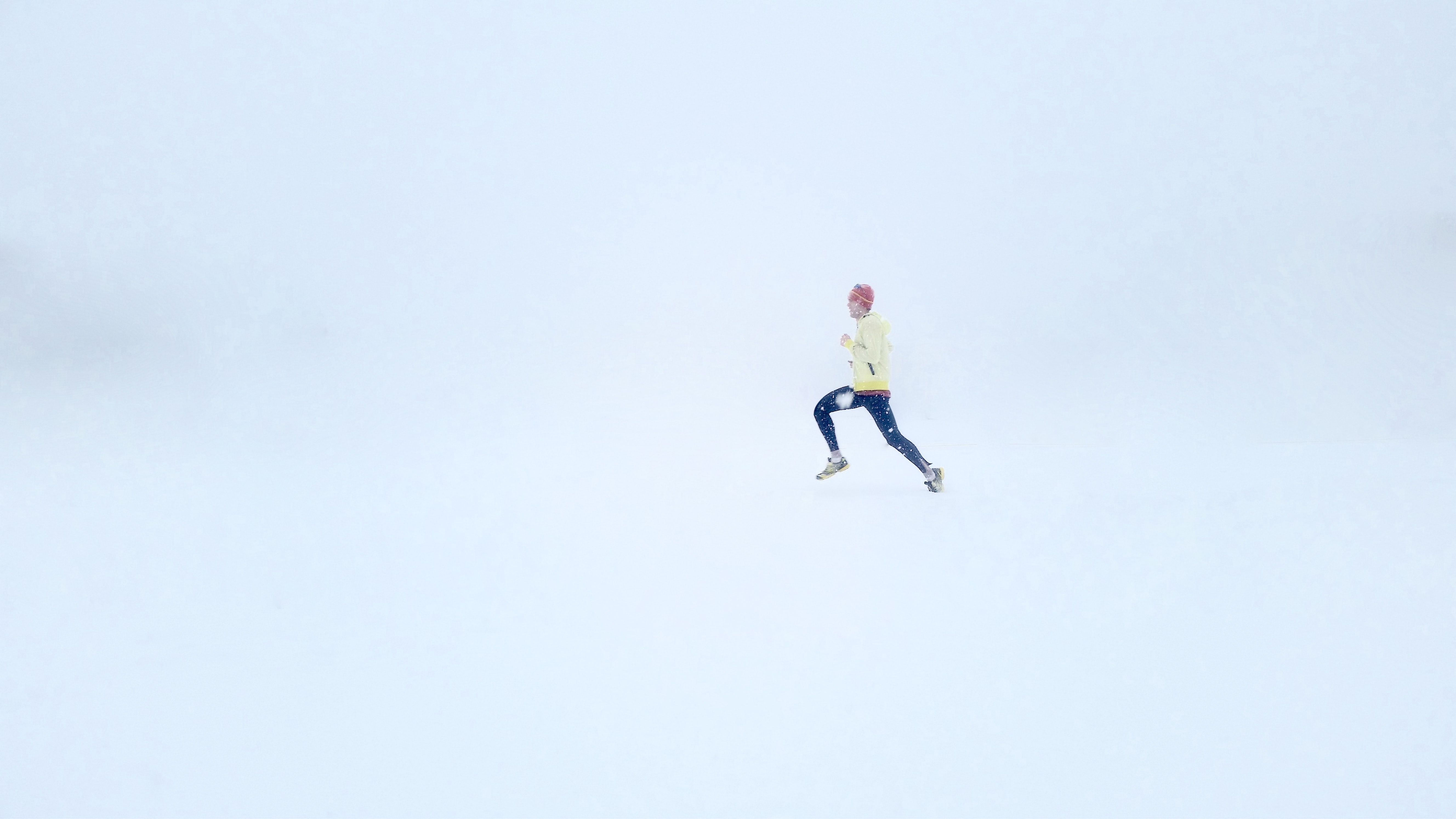 A person running in the snow during a whiteout