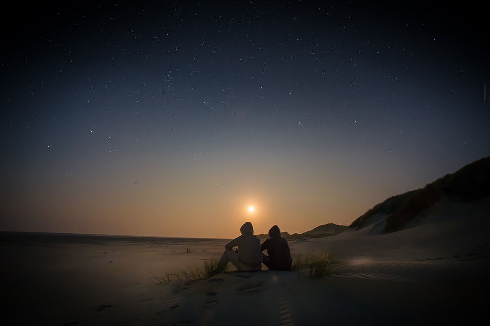 silhouette of two person sitting during golden hour