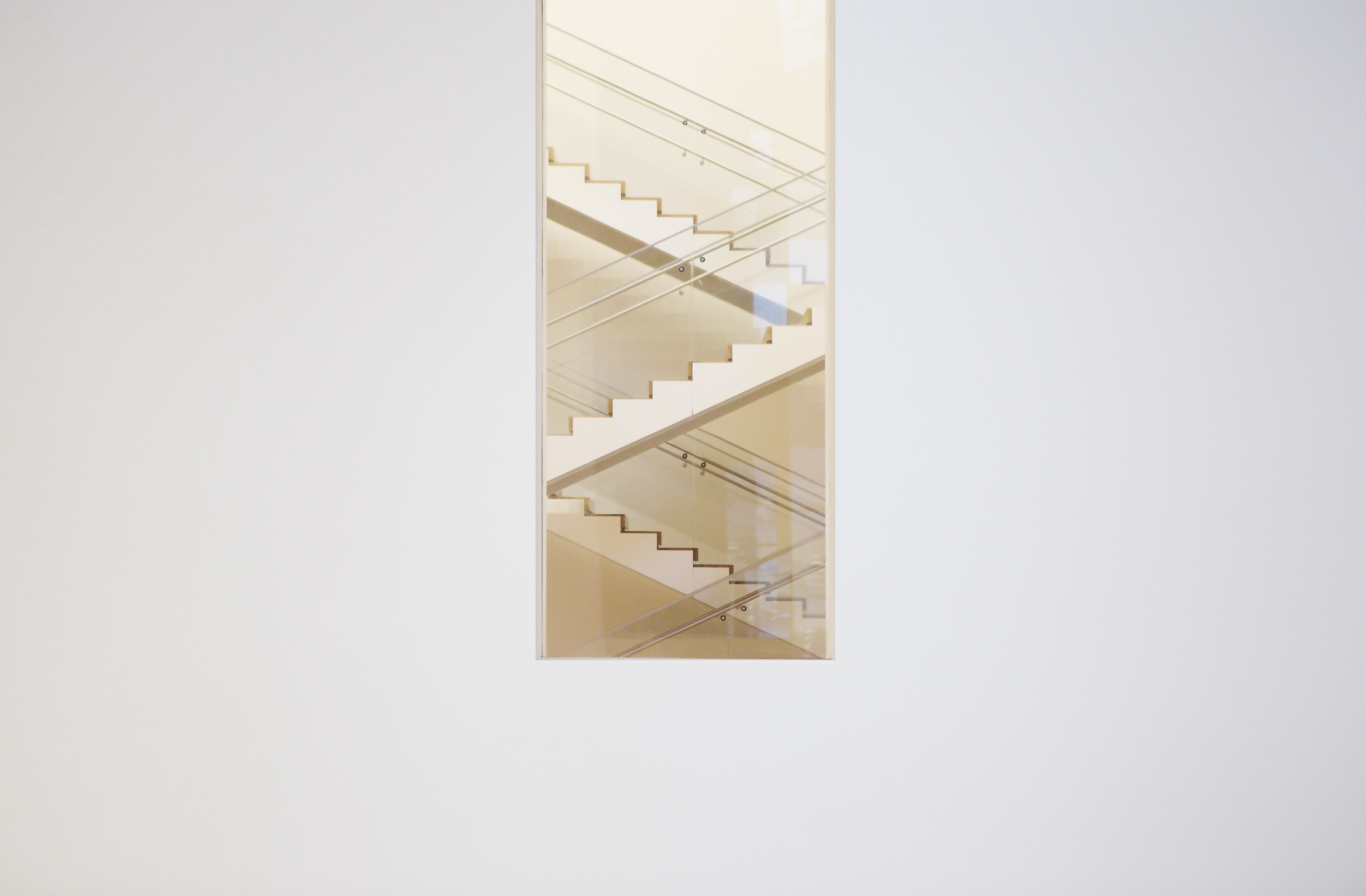 Long shot of zig zag staircase through window in white wall, The Museum of Modern Art
