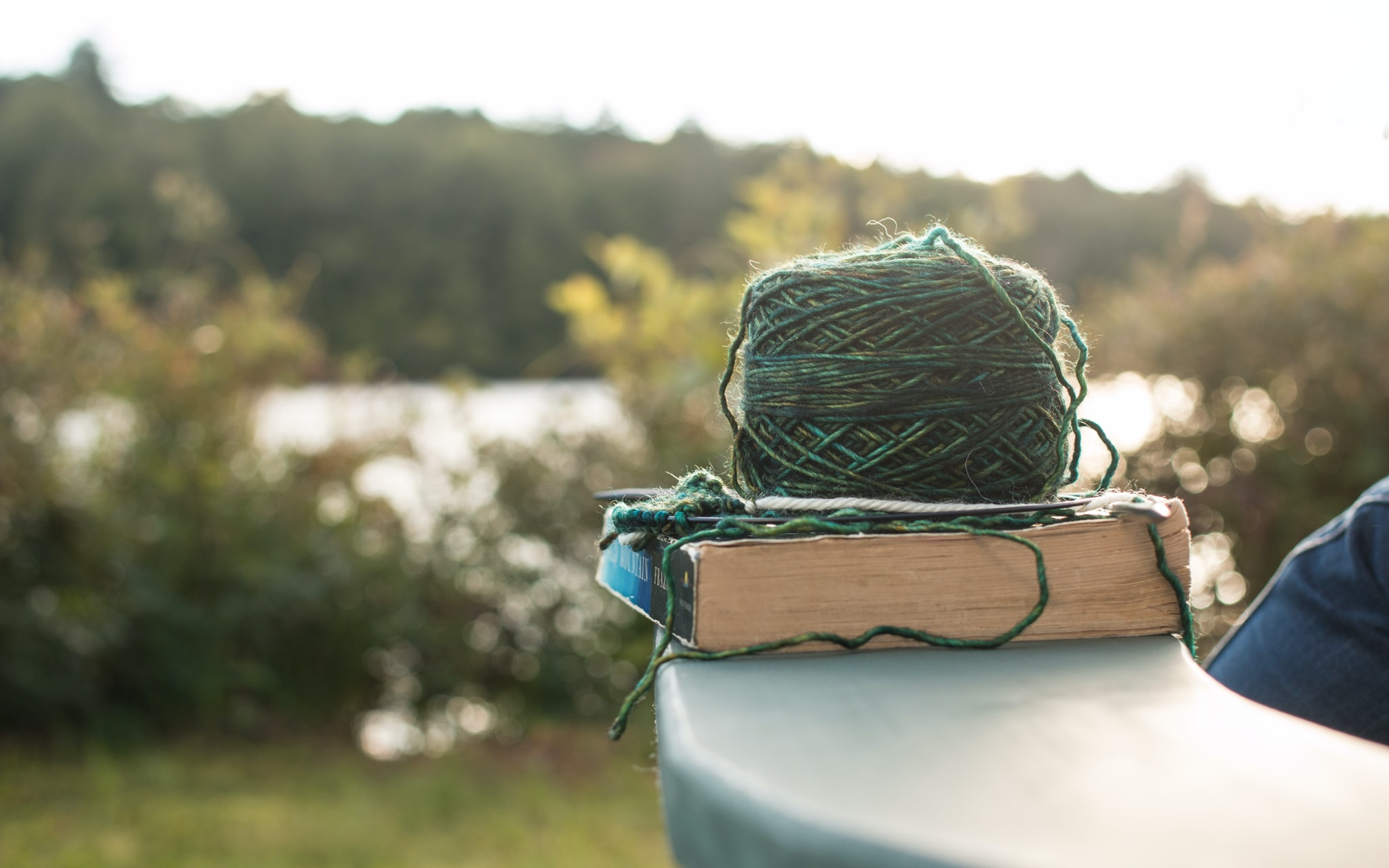 A ball of yarn on a book on a ledge near a lake