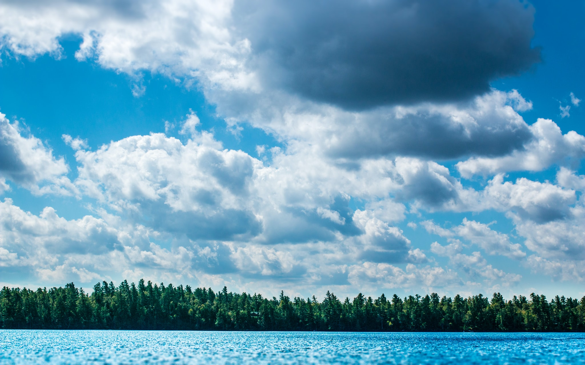 Heavy white clouds over a choppy blue lake
