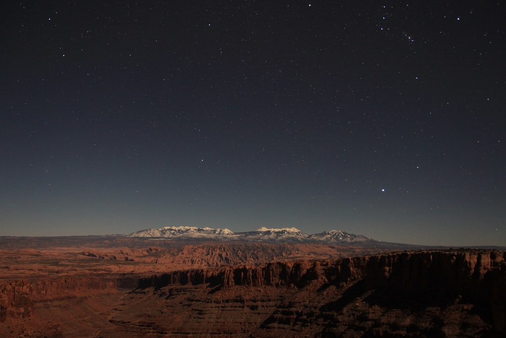 brown mountains under blue sky during night time
