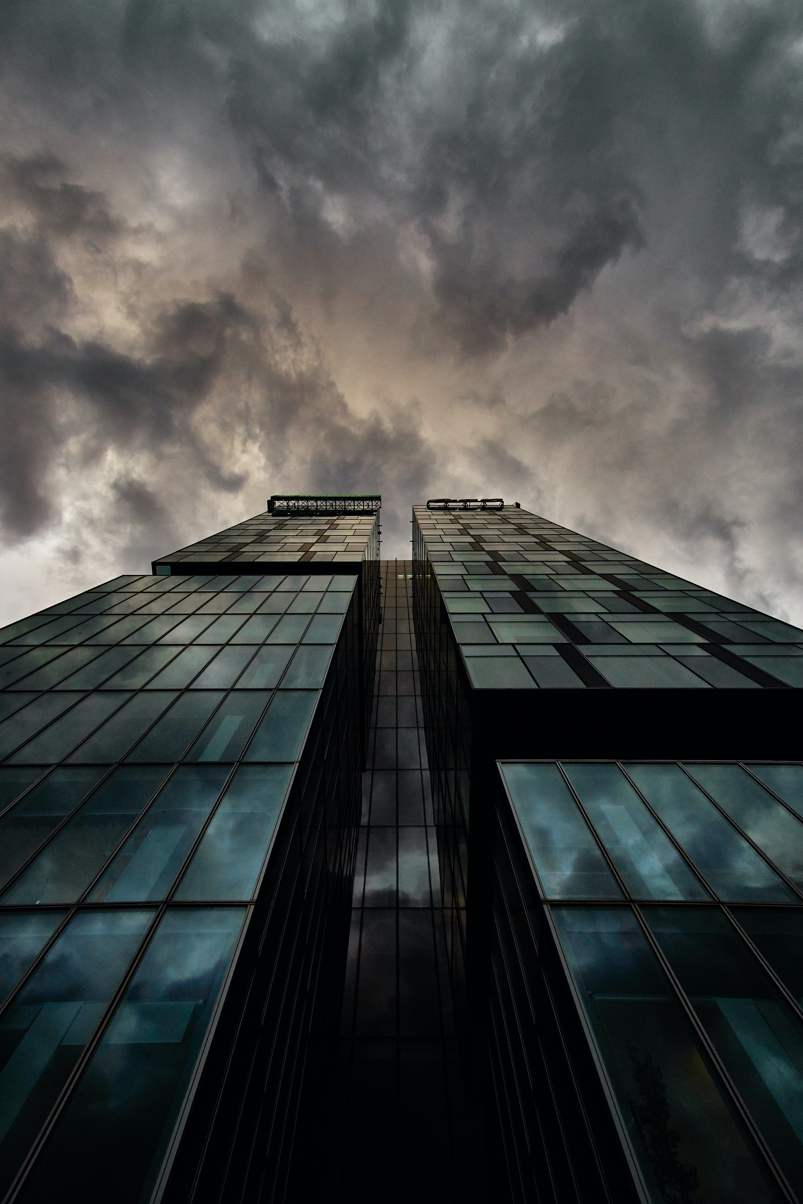 Looking up at dark clouds from the base of a modern skyscraper in Bucharest.