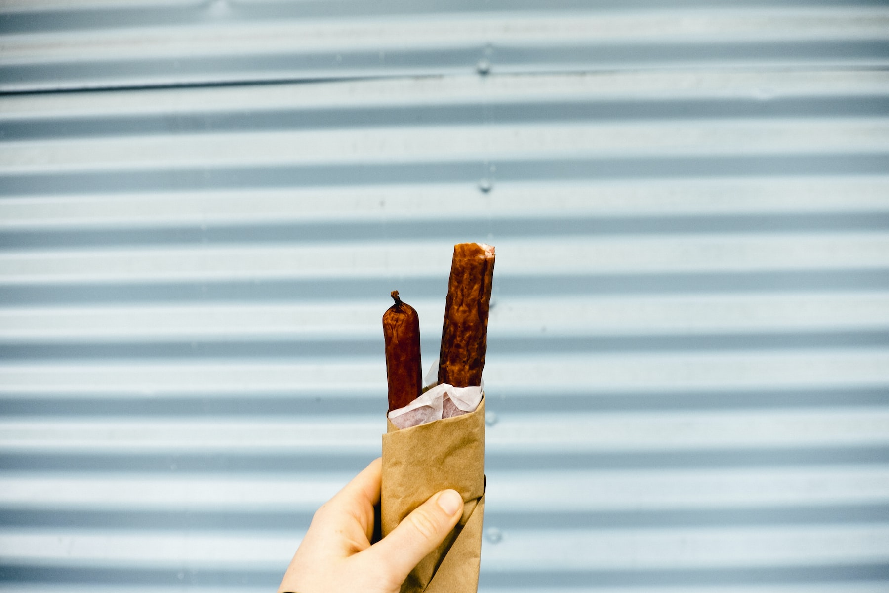 Outstretched hand holding sausage snacks against a gray garage