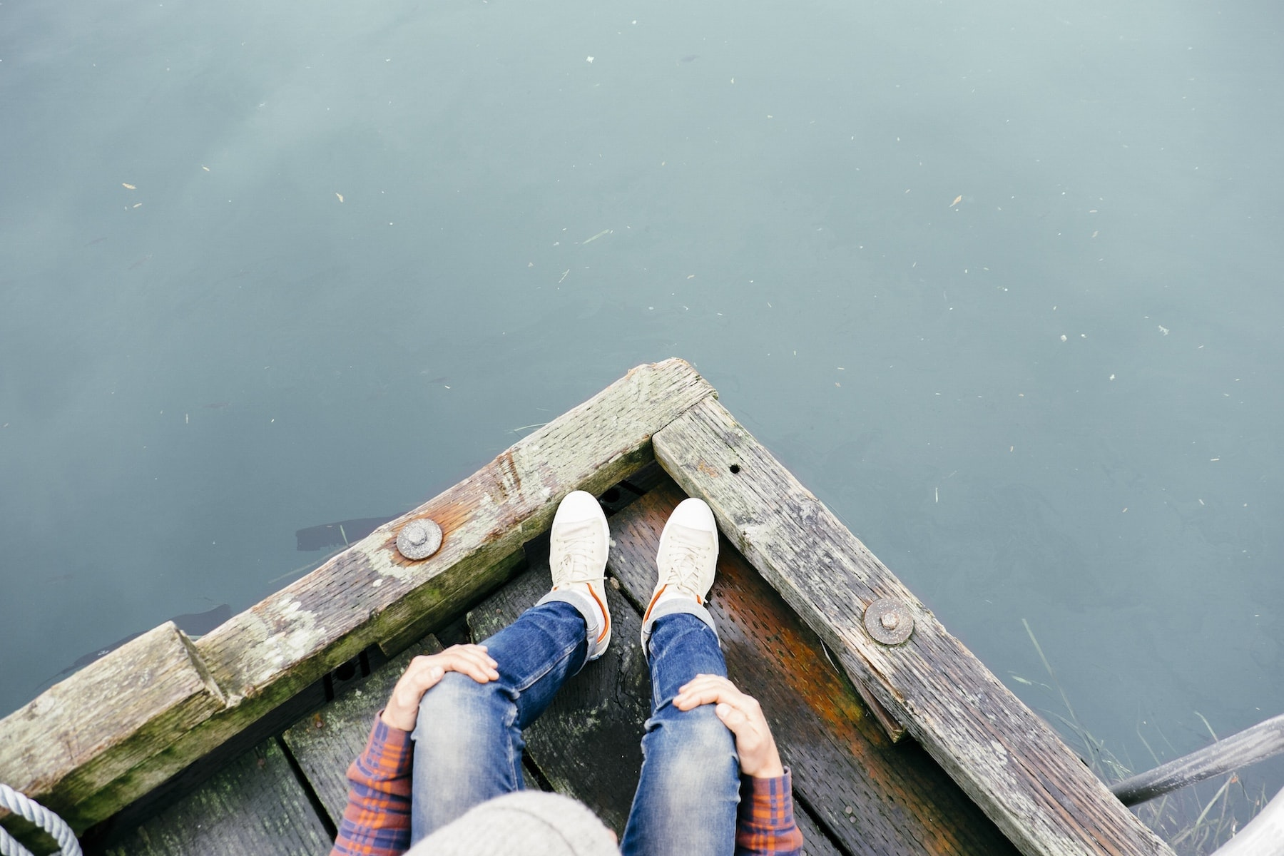 A look down on a person sitting at the edge of a dock wearing jeans and sneakers