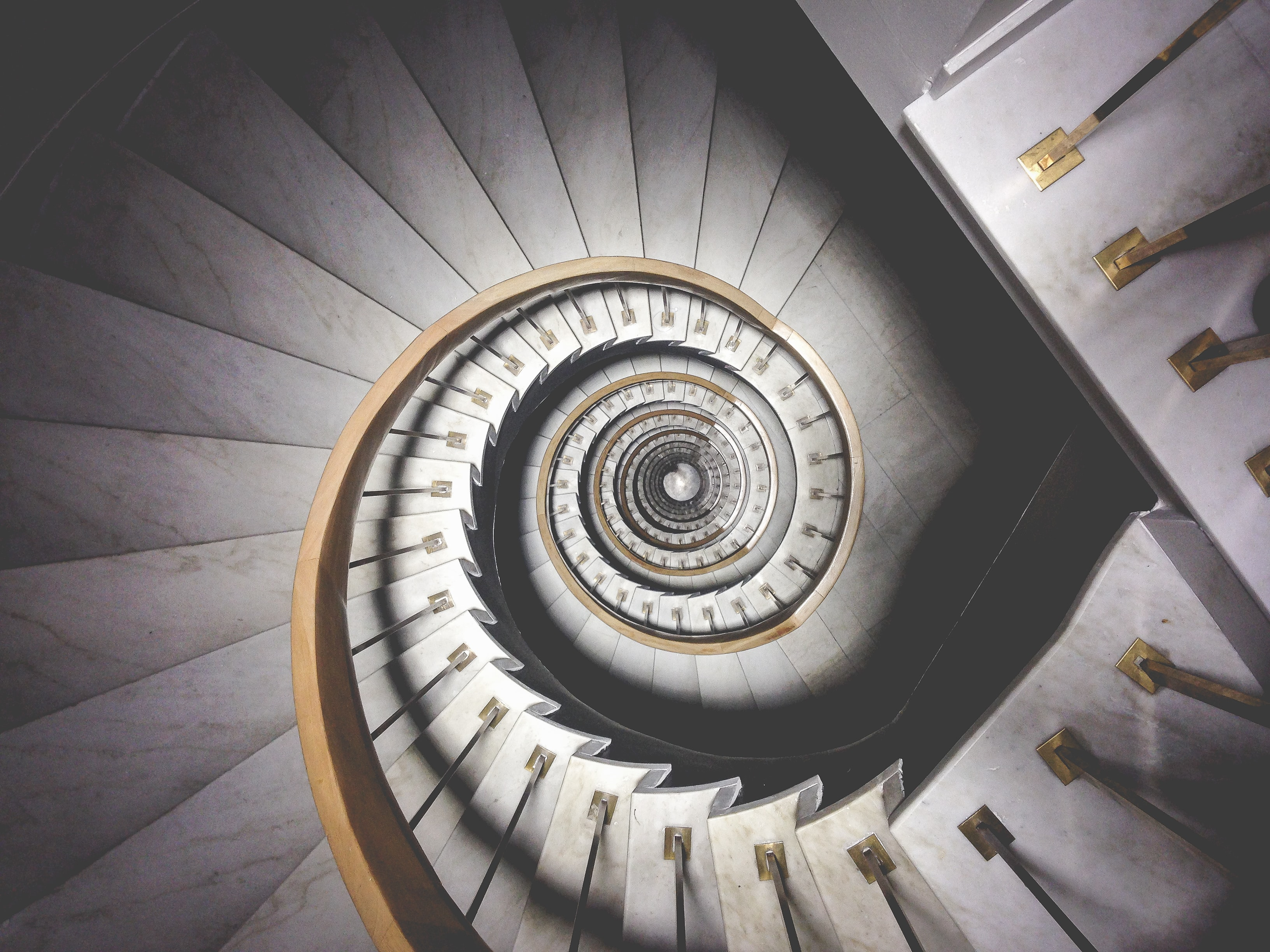 Impressive view down a stairwell with spiral marble stairs