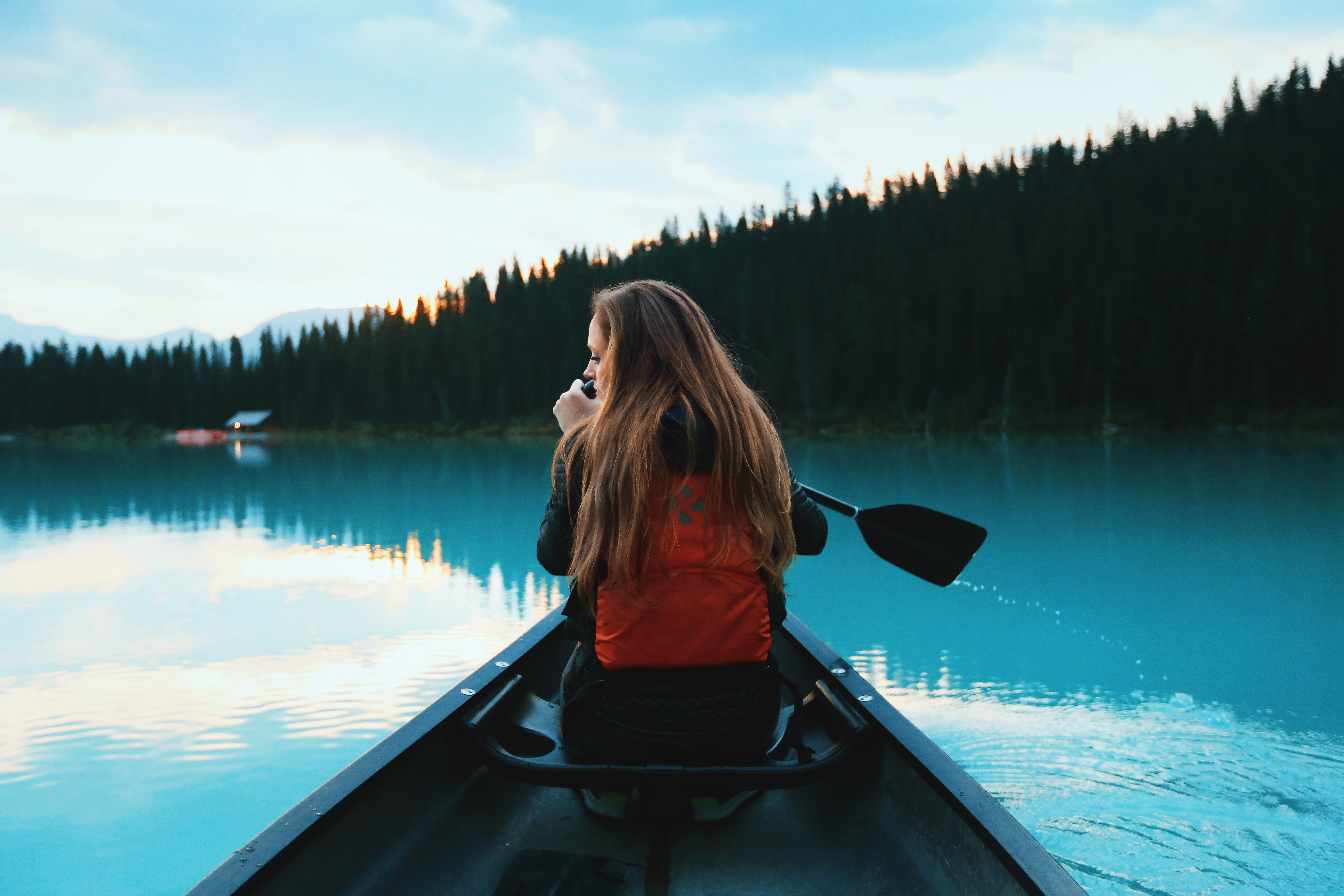 A woman with a backpack in a boat on a blue lake