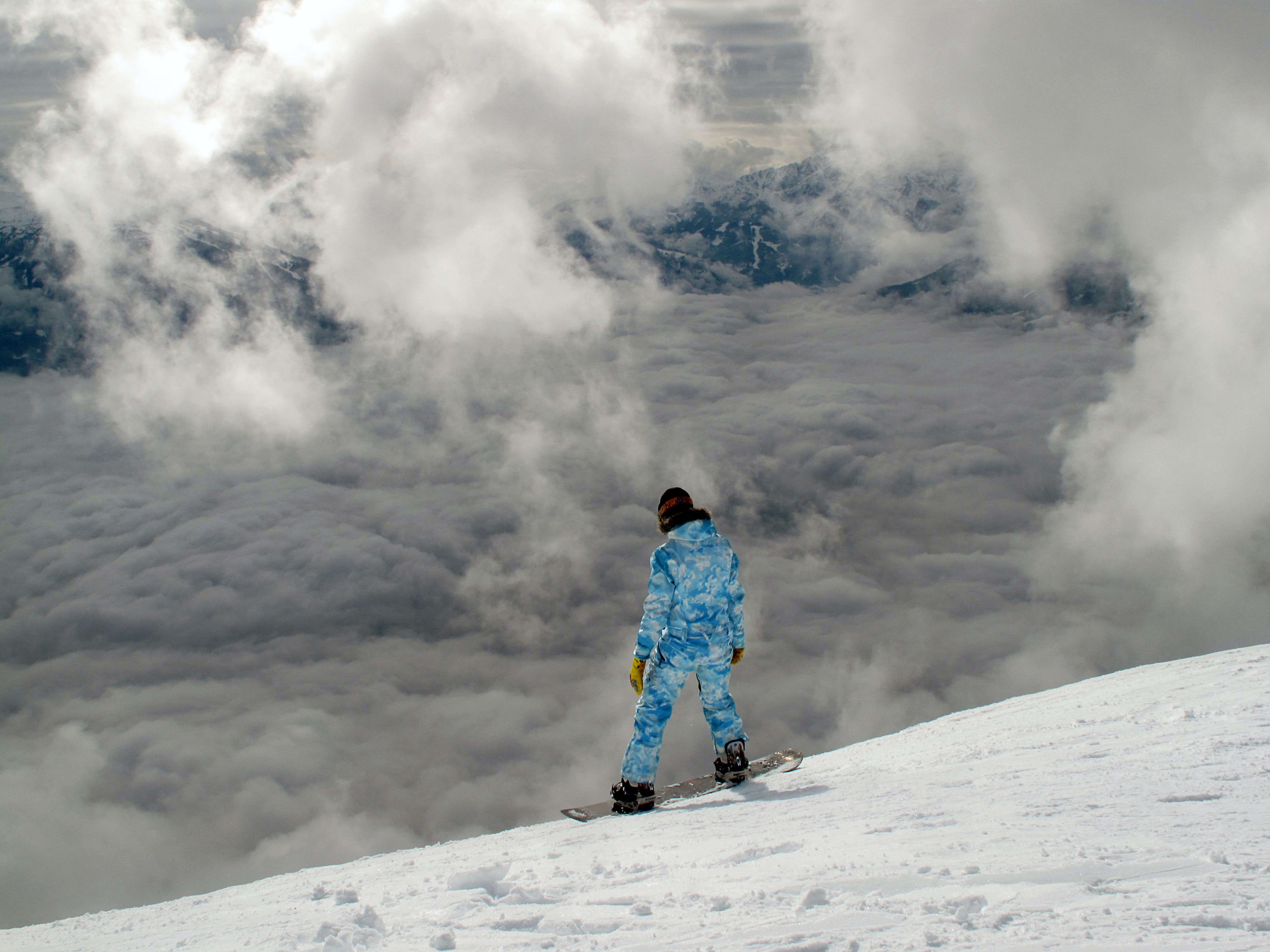 A snowboarder overlooking a cloudy and snow covered hill
