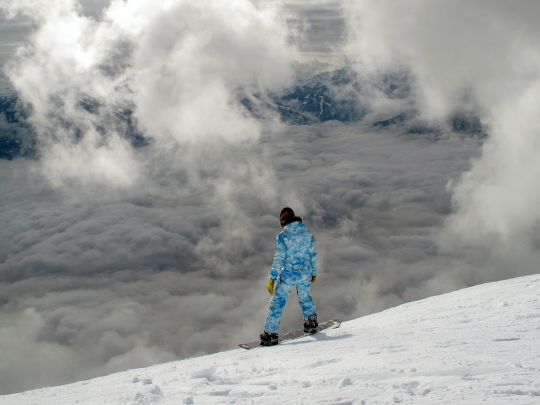 A snowboarder overlooking a cloudy and snow covered hill for Conscious by Chloé