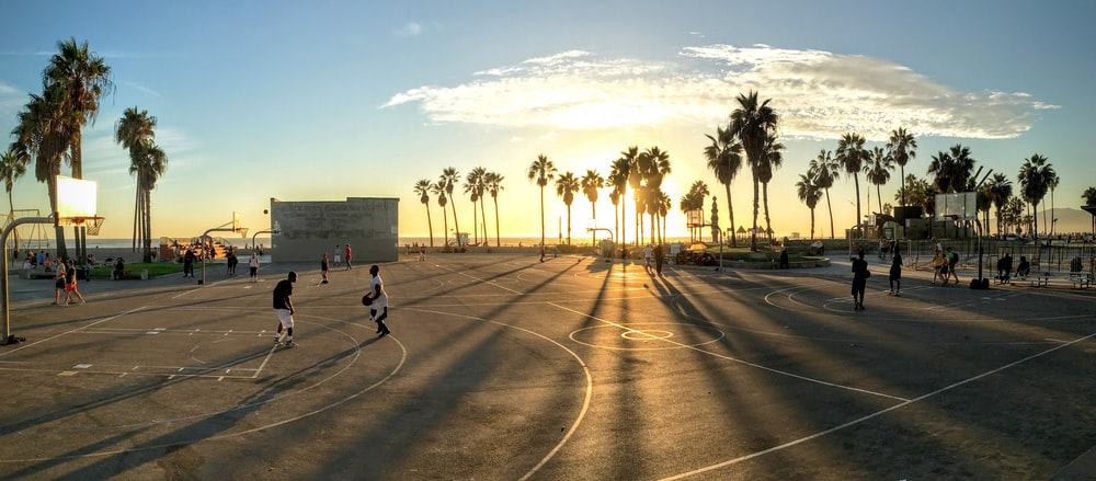 people playing basketball at court during sunset