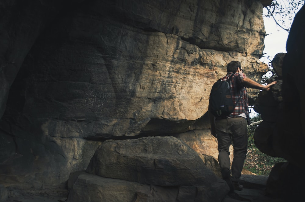 man with backpack at the cave