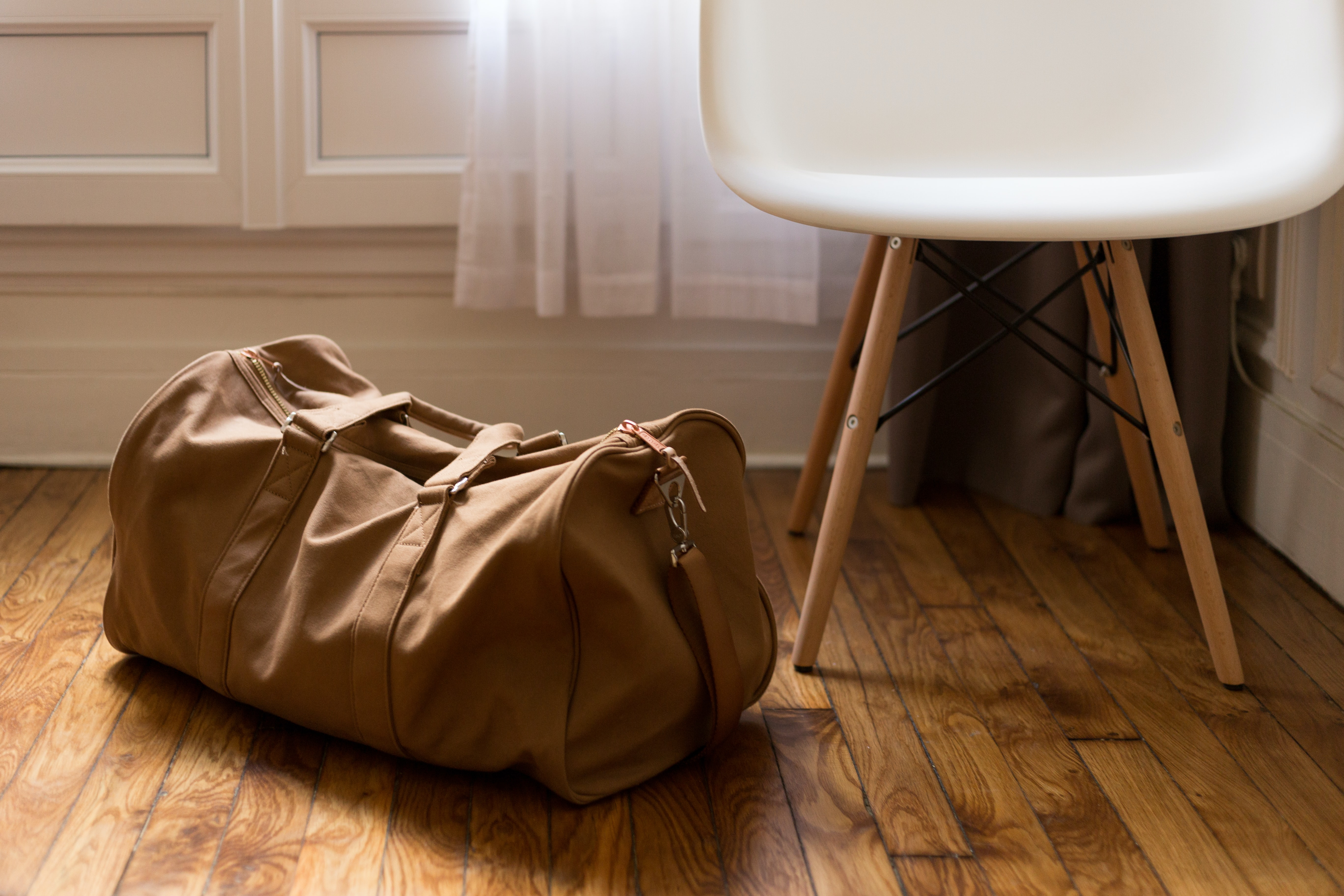 A leather duffel bag on the floor next to a small white chair