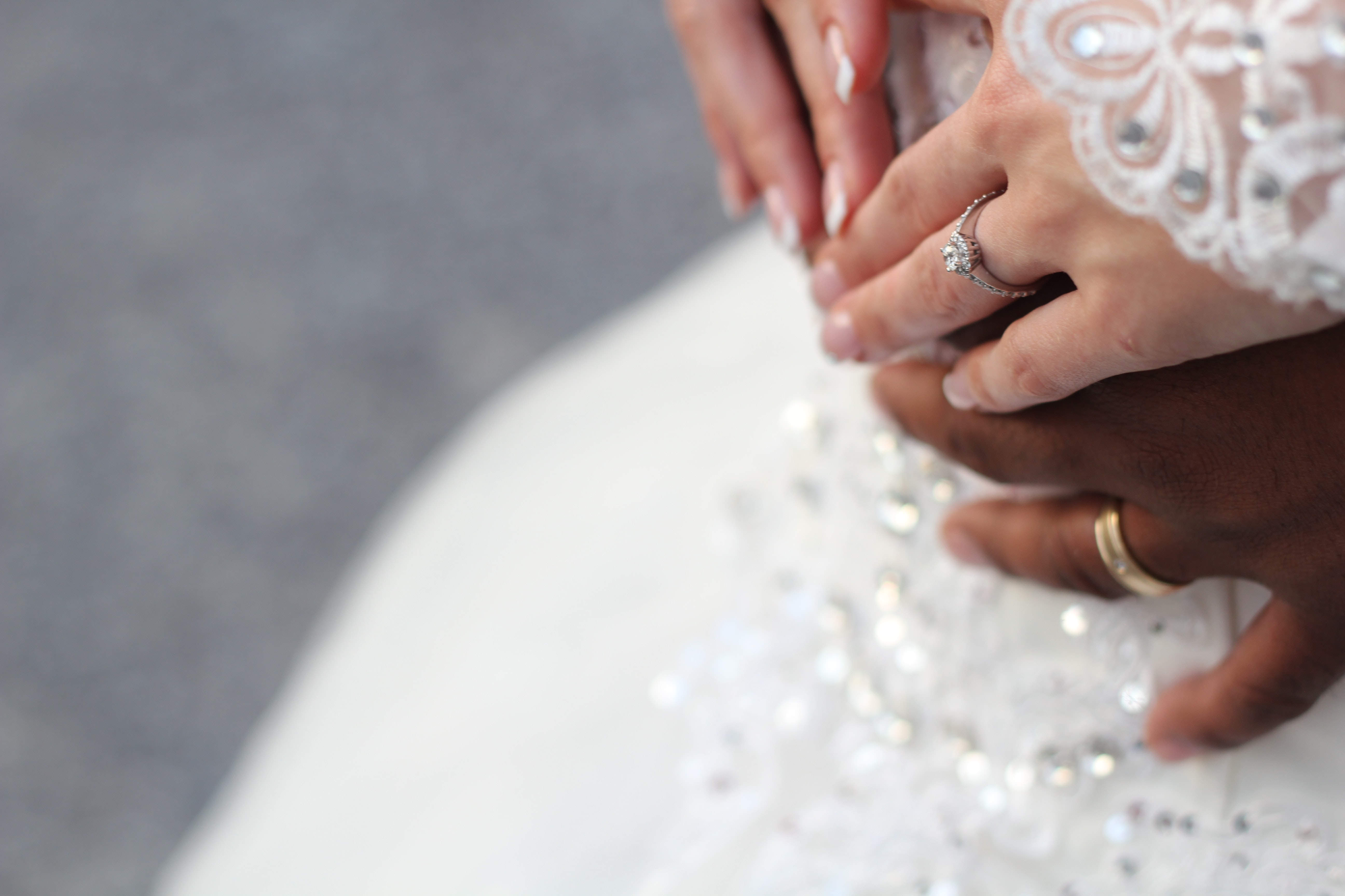 Couple's hands touch gingerly on their wedding day