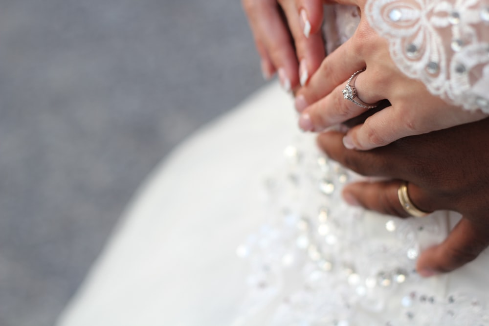people holding hands while wearing gold-colored wedding rings