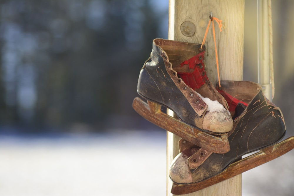 pair of black-and-brown ice skates hanging on brown wooden post