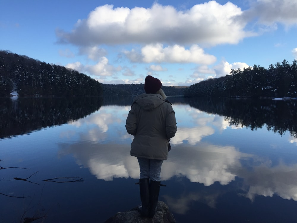 person in gray hoodie in front of body of water