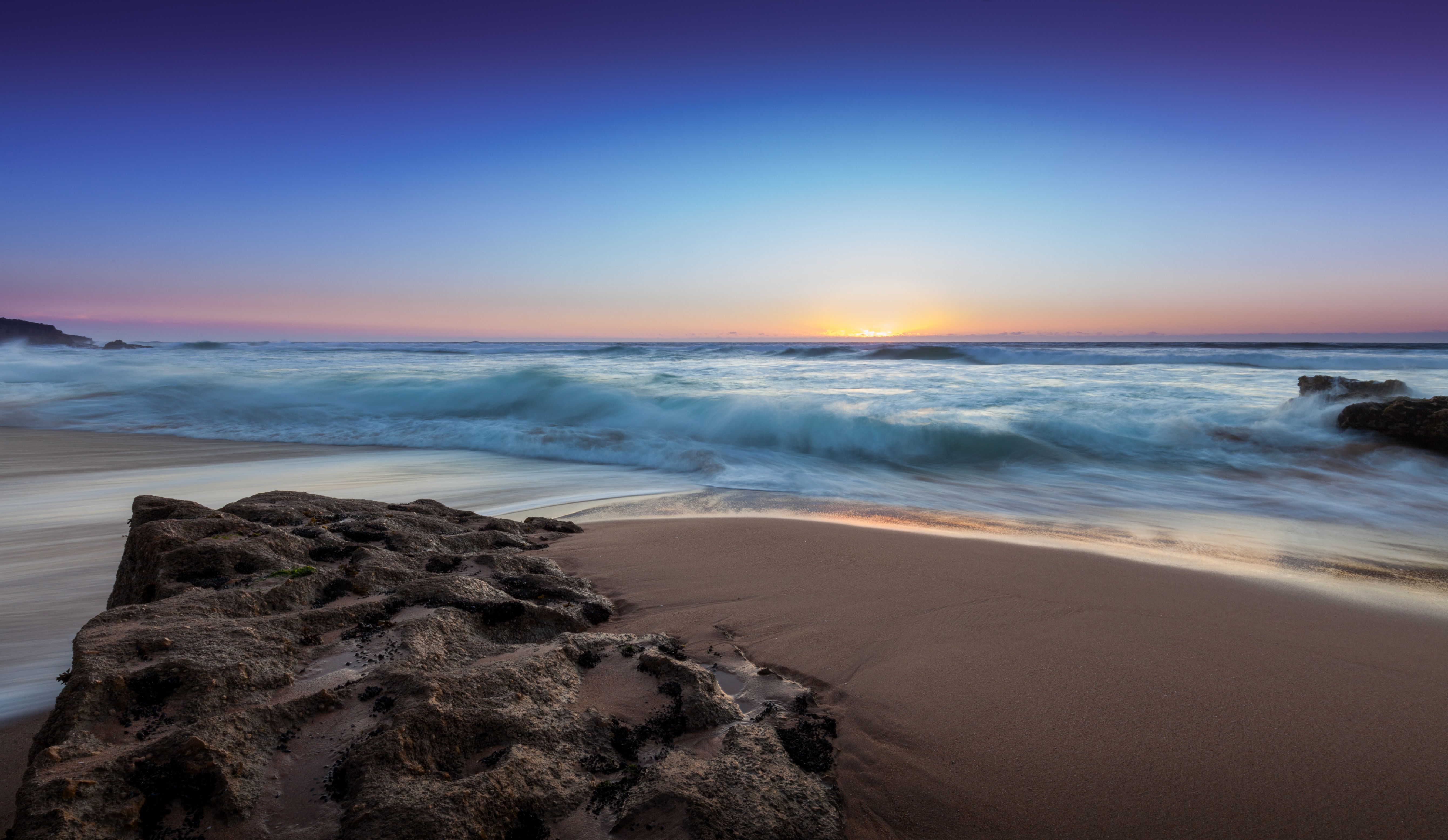 Ocean washing on the Praia do Guincho sand shore at sunset