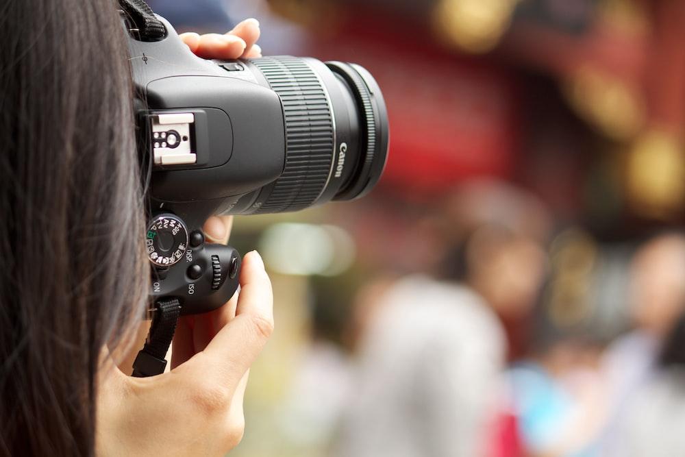 shallow focus photography black Canon DSLR camera