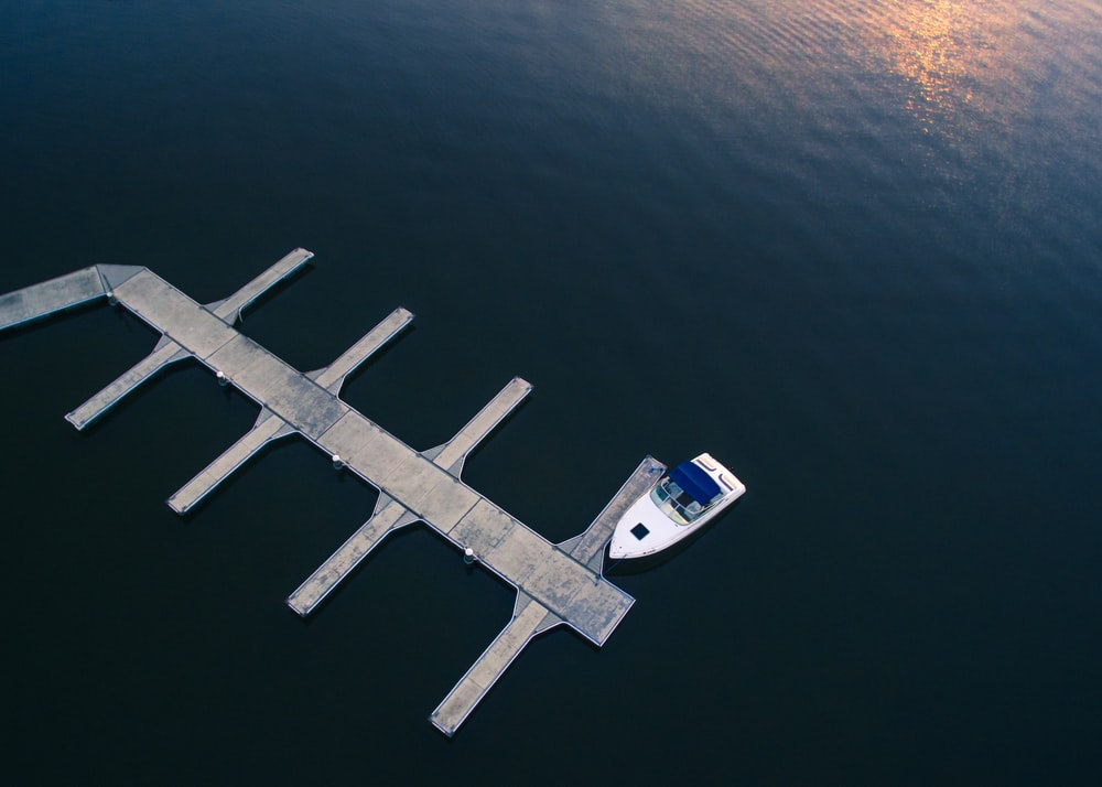 white yacht near dock on body of water