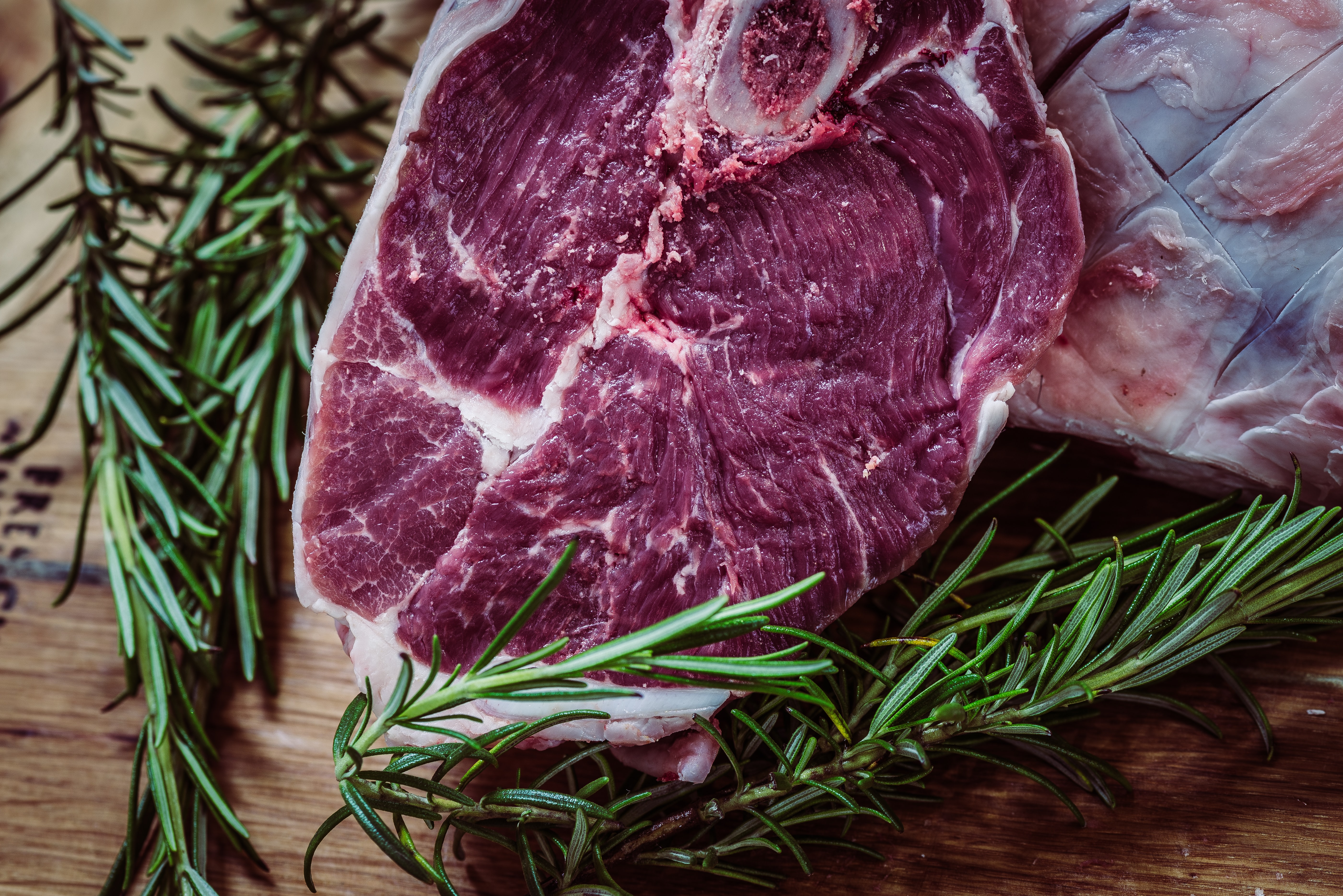 Raw steak with fresh rosemary and herbs on a rustic table