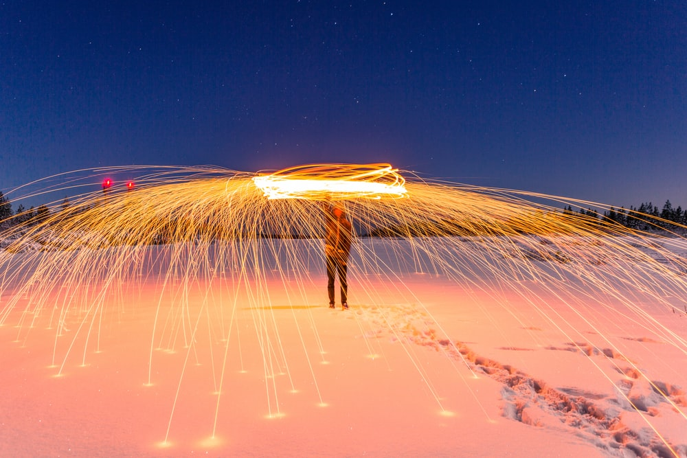 time lapse photography of man performing fire dance