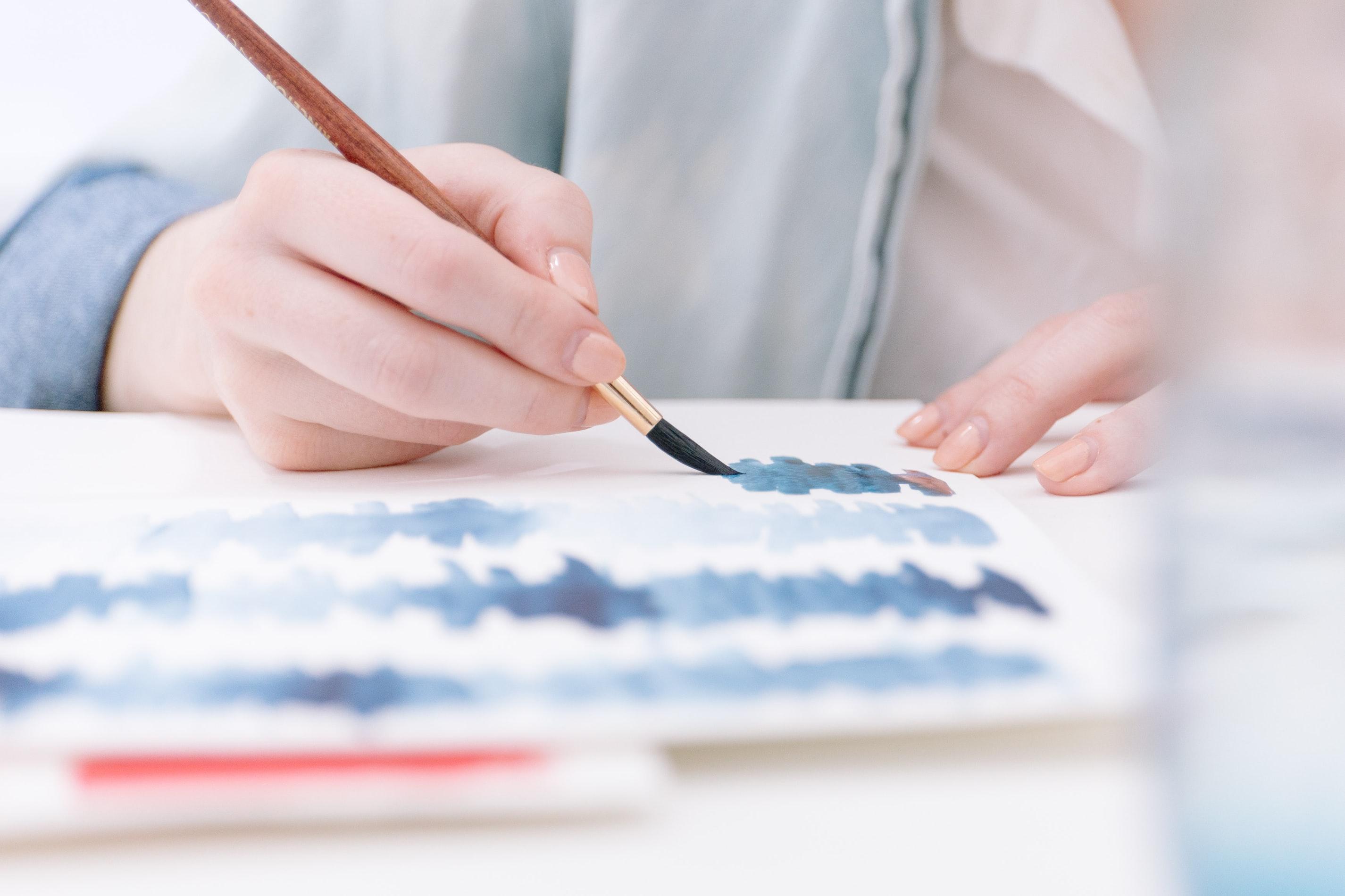 Person malt mit Wasserfarben zur Stressreduktion