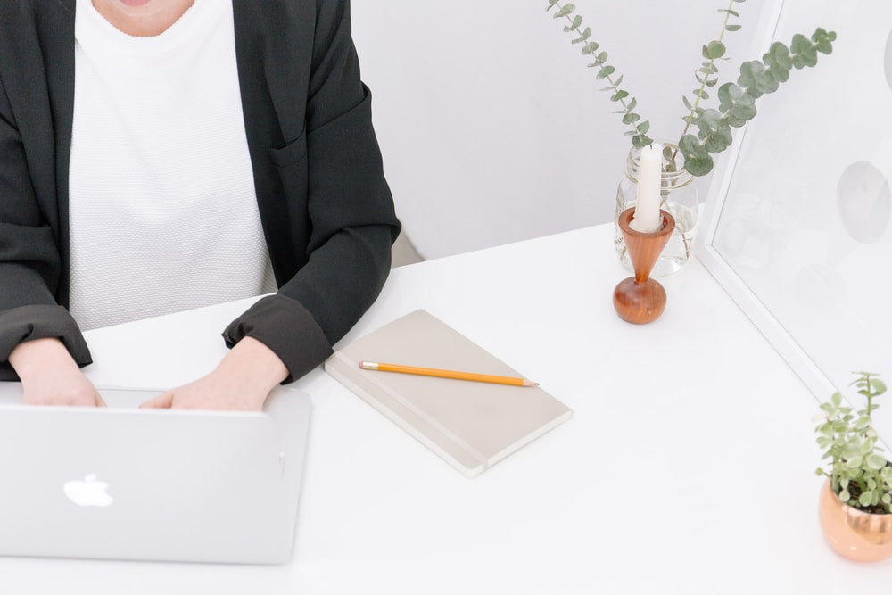 A person in business attire typing on a Macbook.